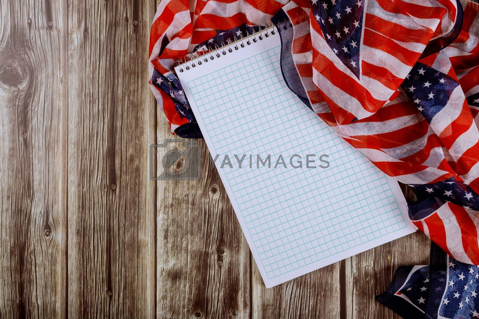 Beautifully waving star striped American flag with notebook on wood table for background