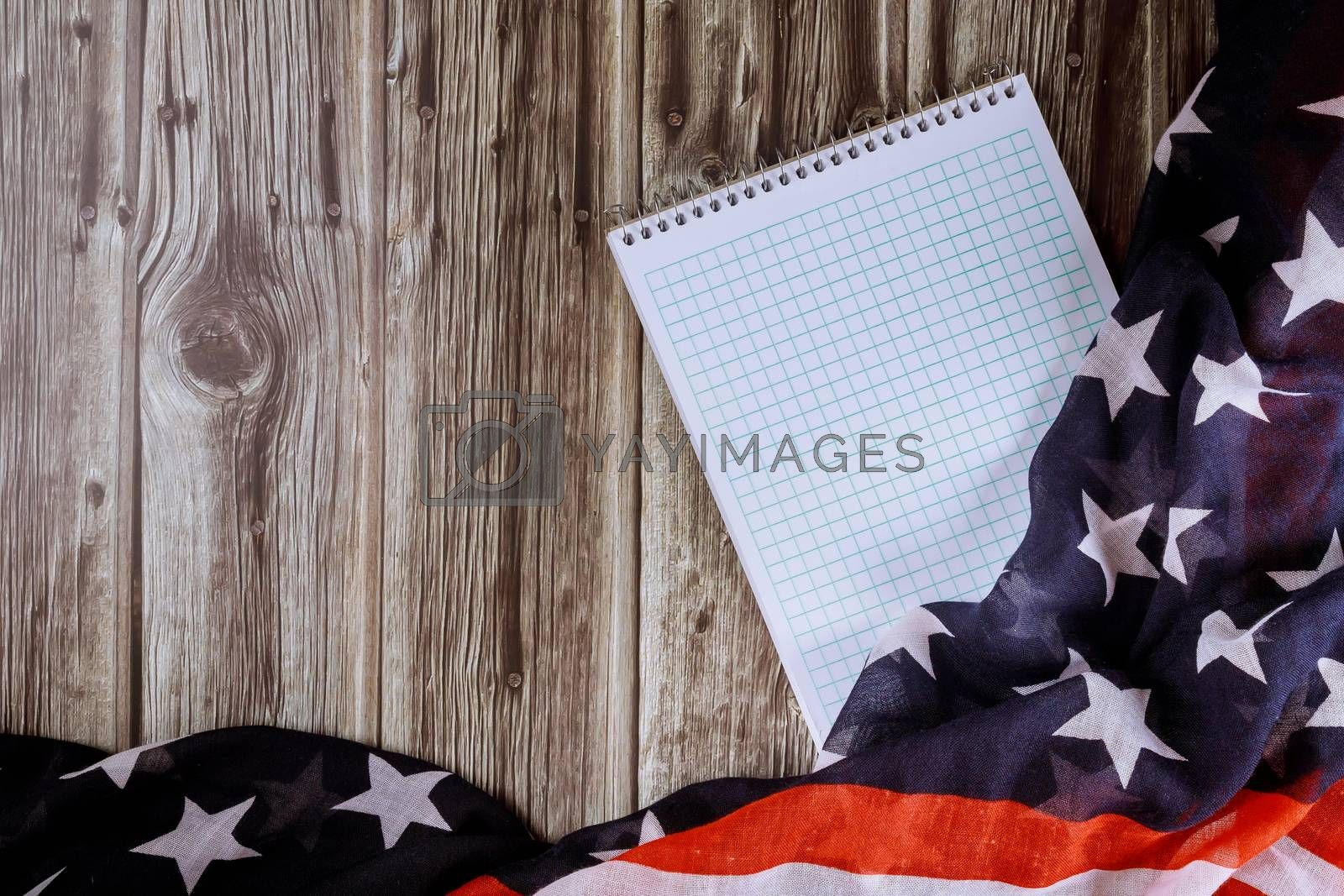 Top view of blank note paper with wood table of ruffled American flag background the national symbol of the USA