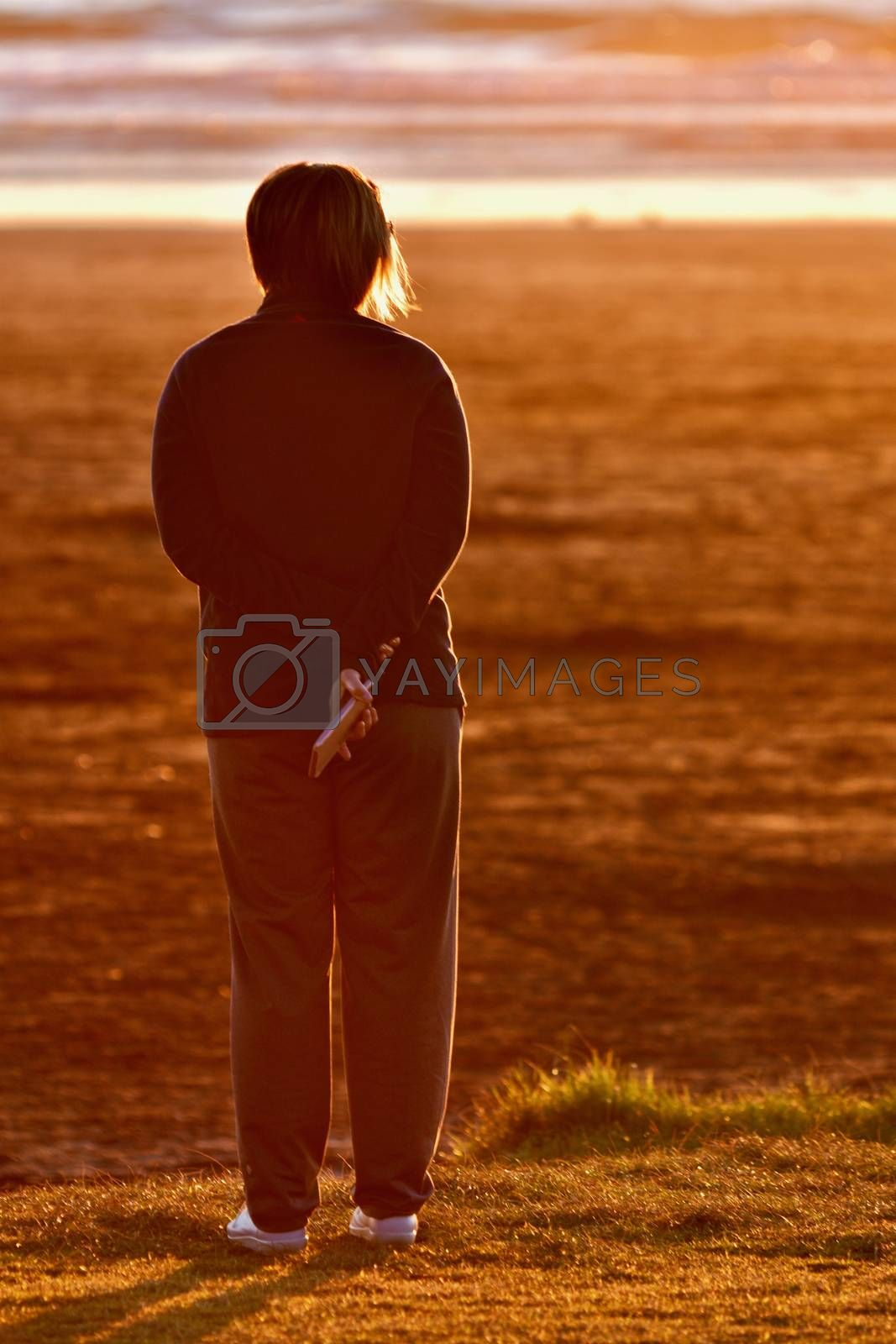 An unidentified person enjoying sunset on a beach.