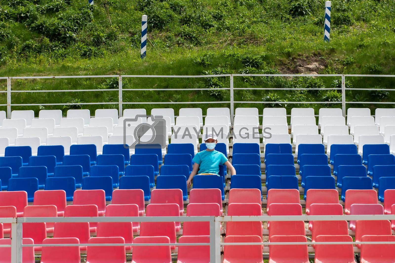 Lonely boy in protective mask on the empty stadium outdoor. Empty tribune due to pandemic Covid-19. Concept of pandemic life , empty stadiums, distance from viewers, safety.