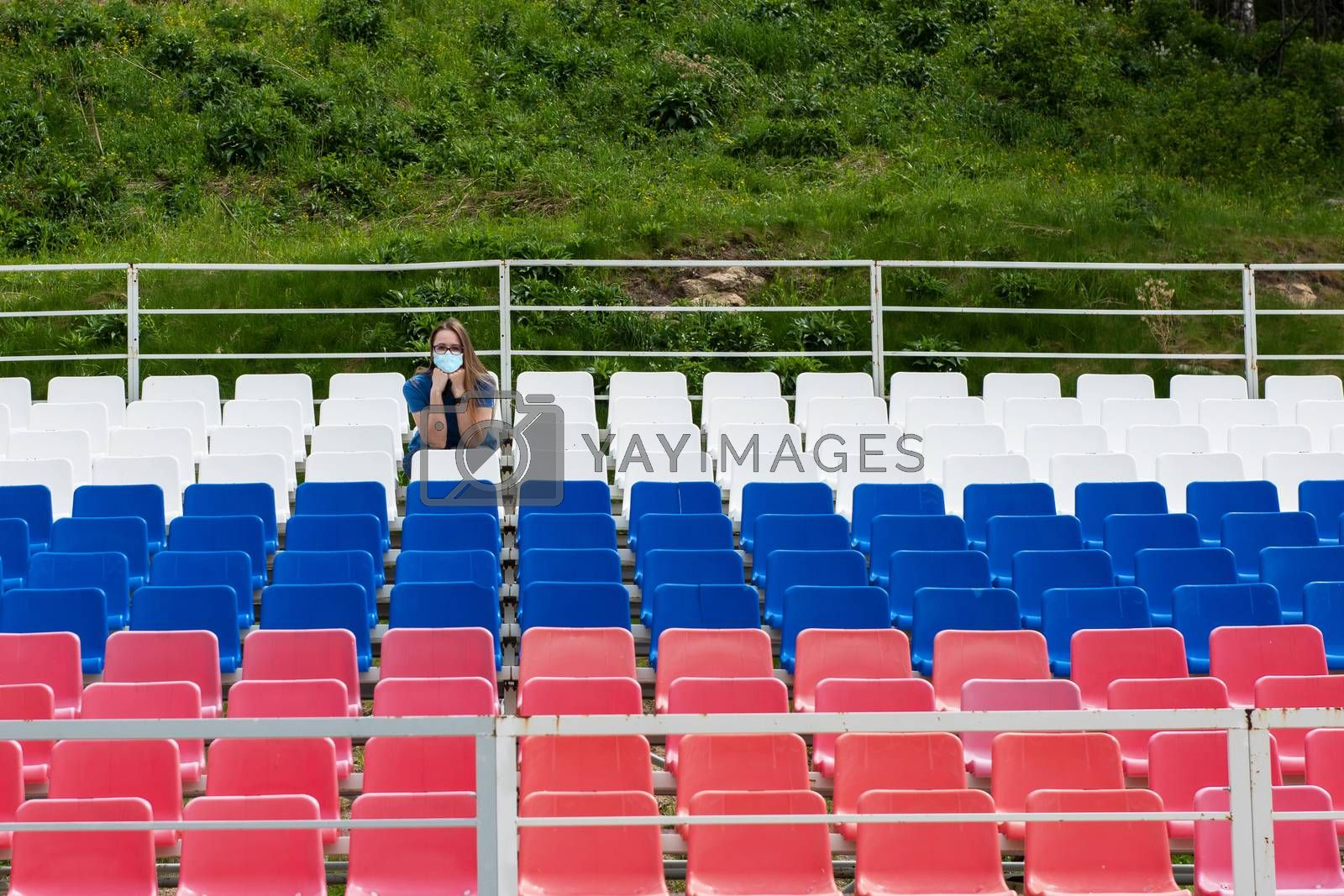 Lonely woman with protective mask on the empty stadium outdoor. Empty tribune due to pandemic Covid-19. Concept of pandemic life , empty stadiums, distance from viewers, safety.
