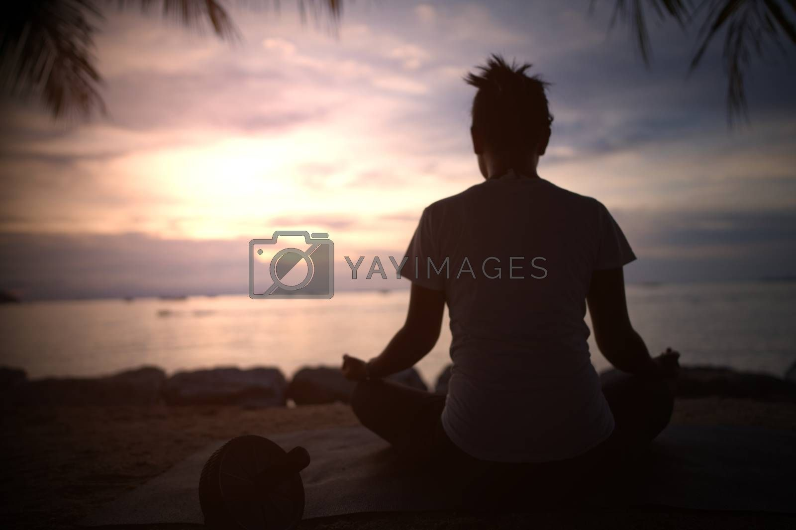 The silhouette of a beautiful woman practicing yoga on the beach during the red and orange summer sunset.