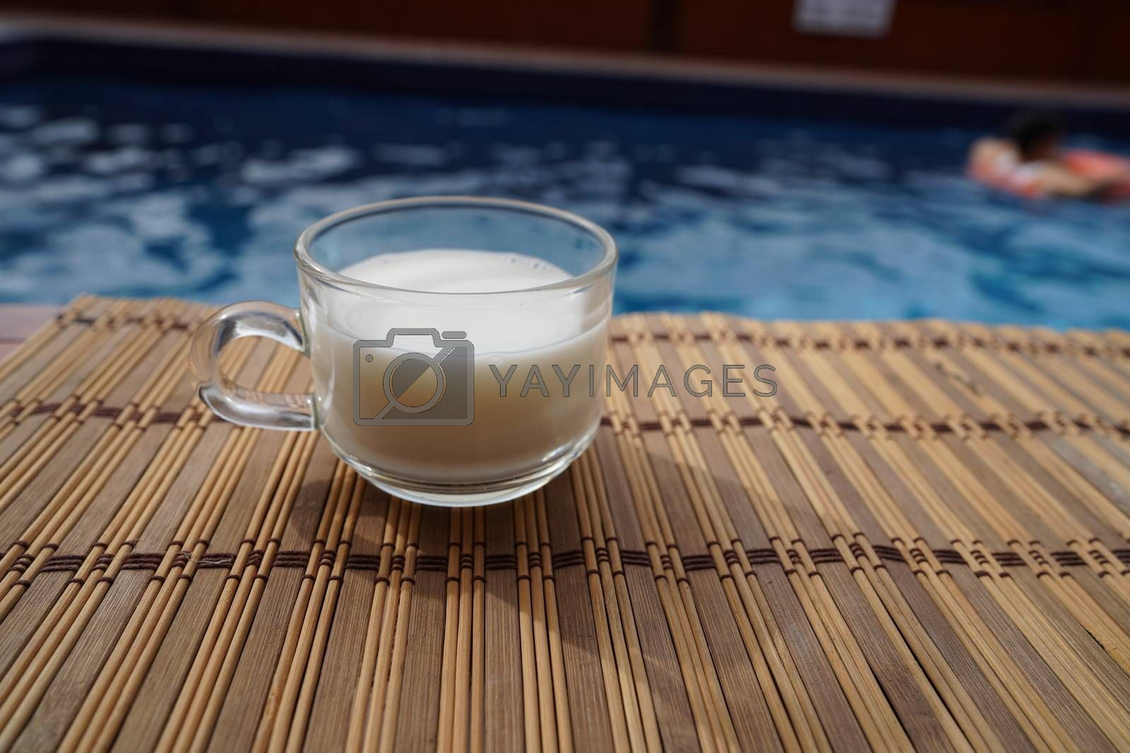 A cup of hot latte coffee is beside the pool in the house.