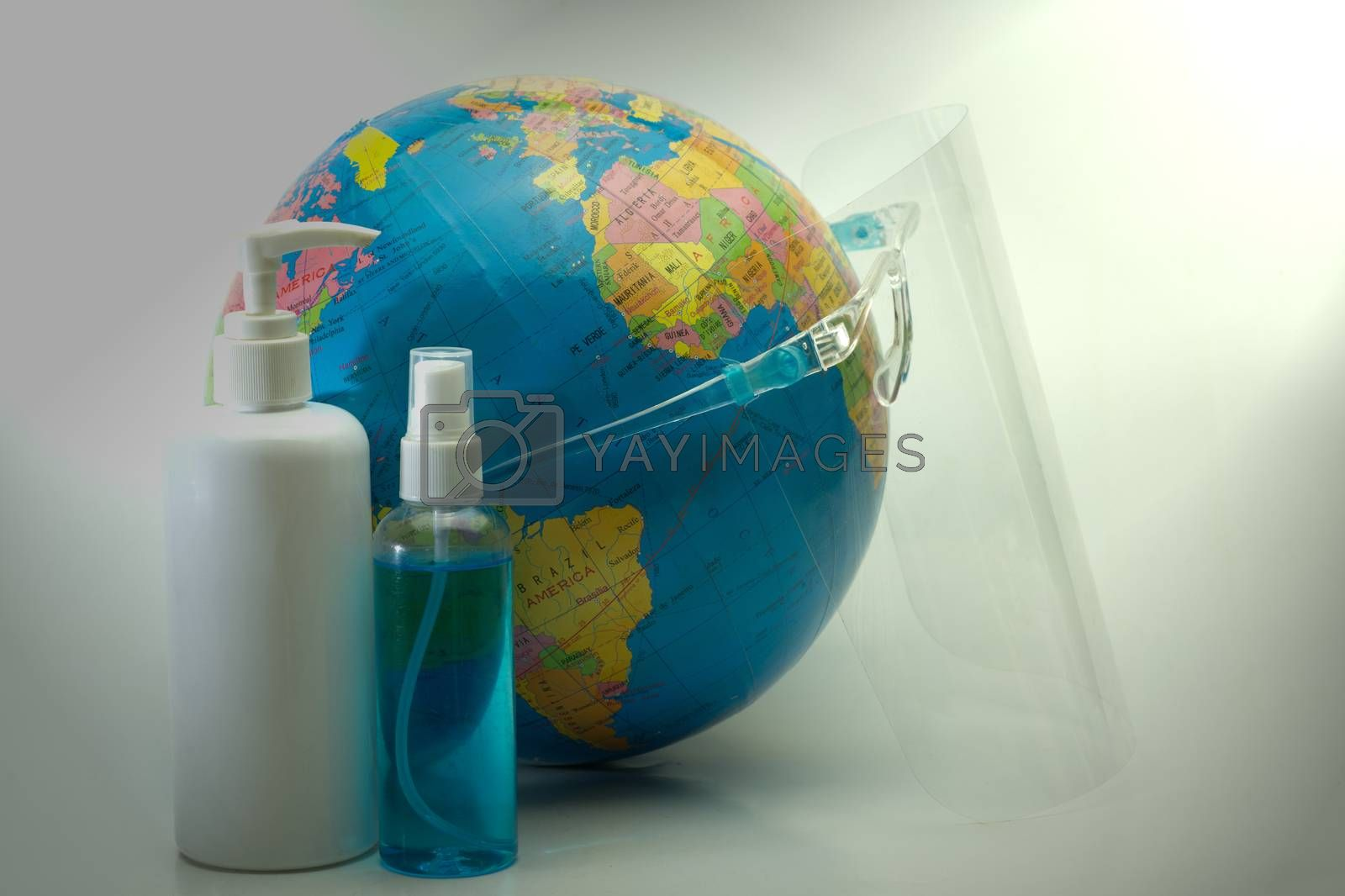 Abstract wearing a face mask SHIELD globe simulates alcohol spray and antiseptic to prevent the spread of the covid-19 virus.