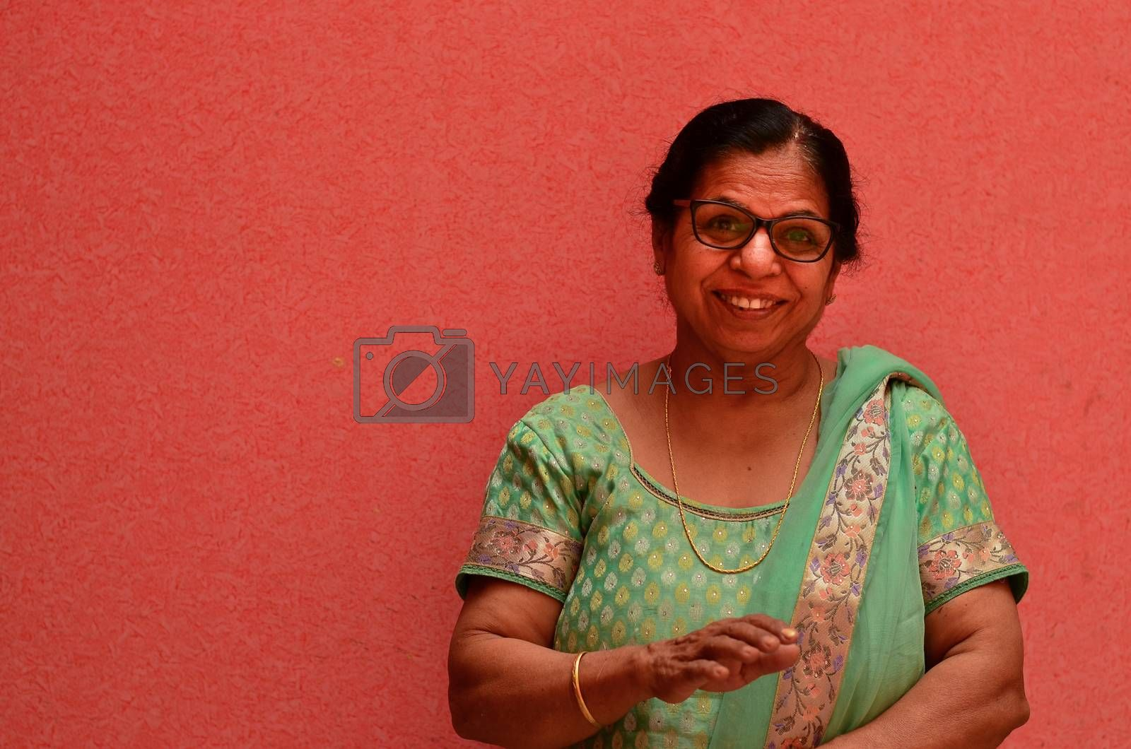 Happy looking senior Indian lady wearing traditional suit and spectacles standing against a pink wall in pink city Jaipur, Rajasthan, India