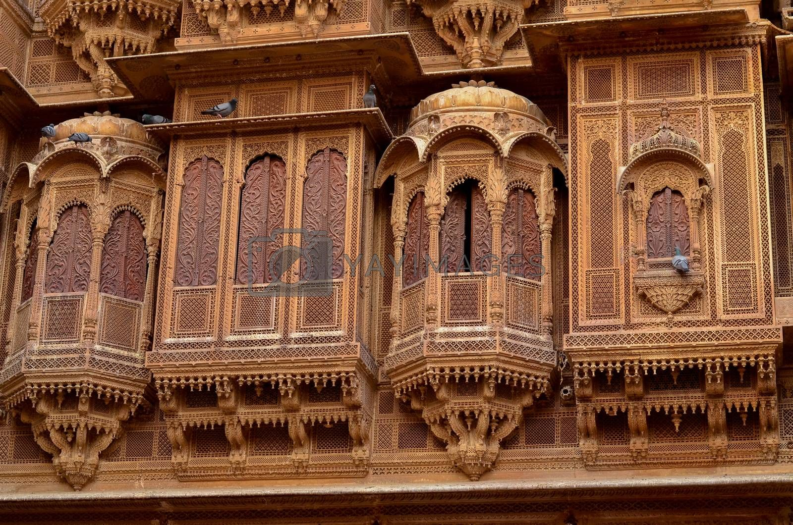 Traditional Rajasthani haveli with a decorated window at Patwon ki haveli in Jaisalmer, Rajasthan, India. Series of early-1800s palaces, now a museum featuring intricate carvings, furniture & artwork.