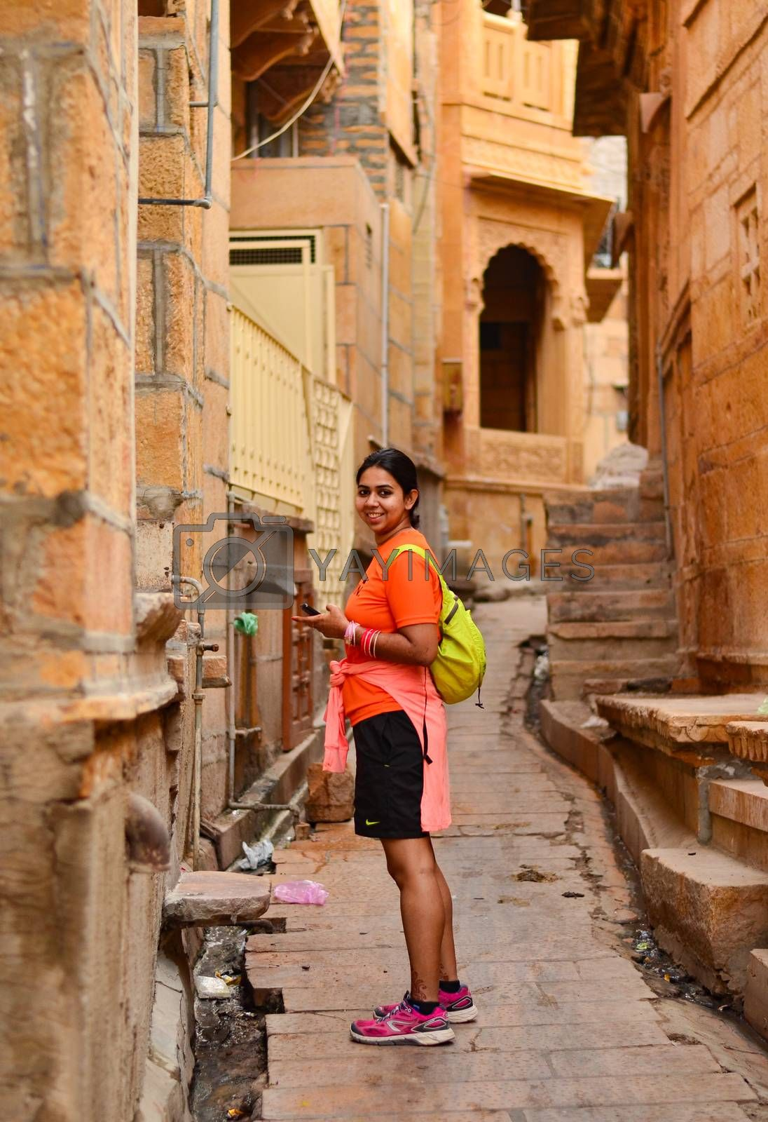 Young woman posing in the by-lanes of Jaisalmer, Rajasthan. Jaisalmer is also known as the golden city because of the Jaisalmer Fort which is golden in colour.