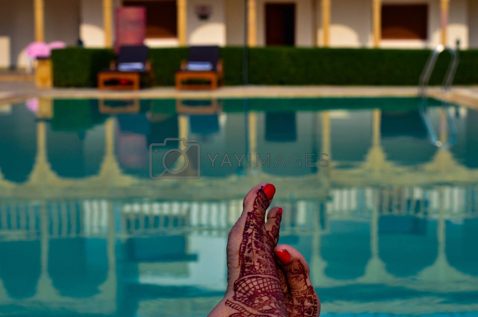 Newly married woman with henna feet in front of a swimming pool on her honeymoon in a resort in Jaisalmer, India