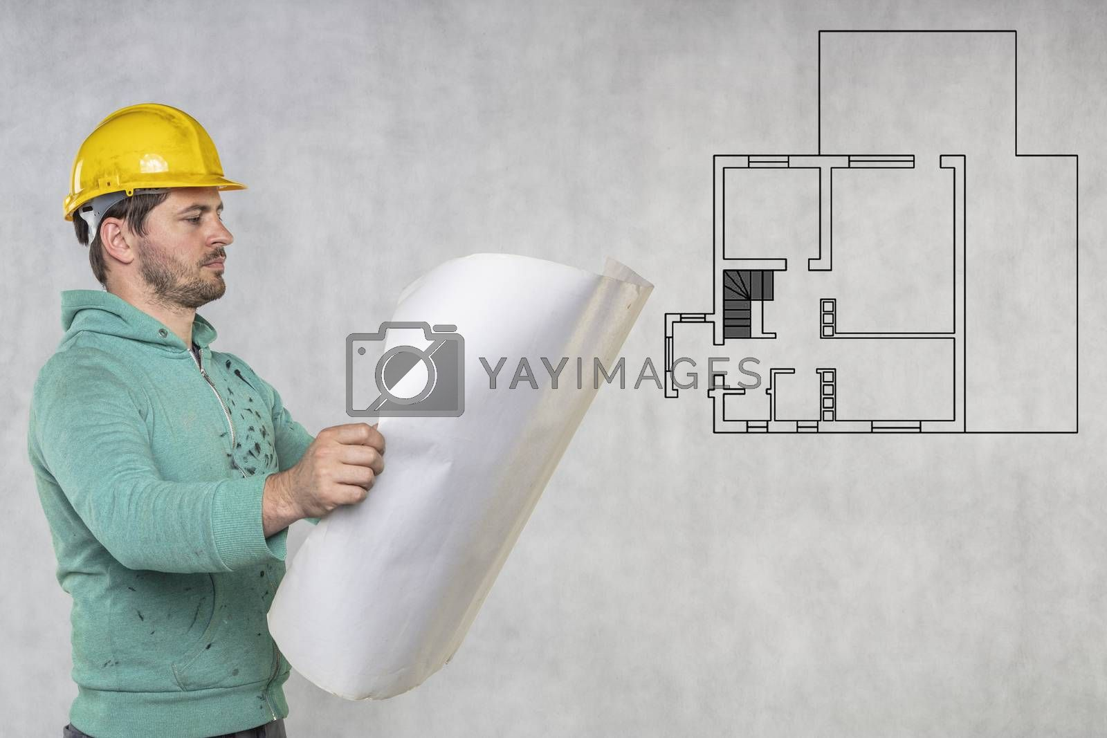 builder and construction plans of apartment, copy space next to him