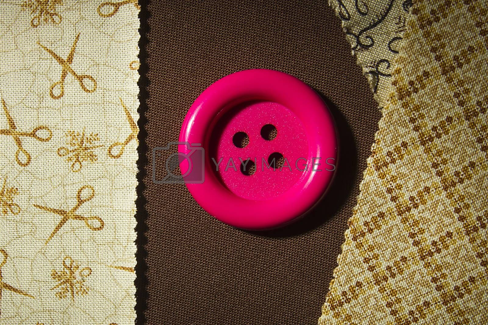 Button and fragments of fabric on a wooden table