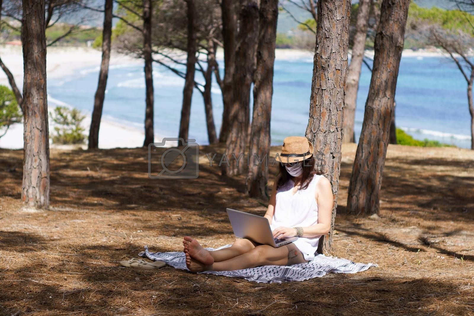 Freelance woman working in vacation on the laptop sitting in a pine forest on the sea with face mask protection for coronavirus, smart working lifestyle concept theme and life choice