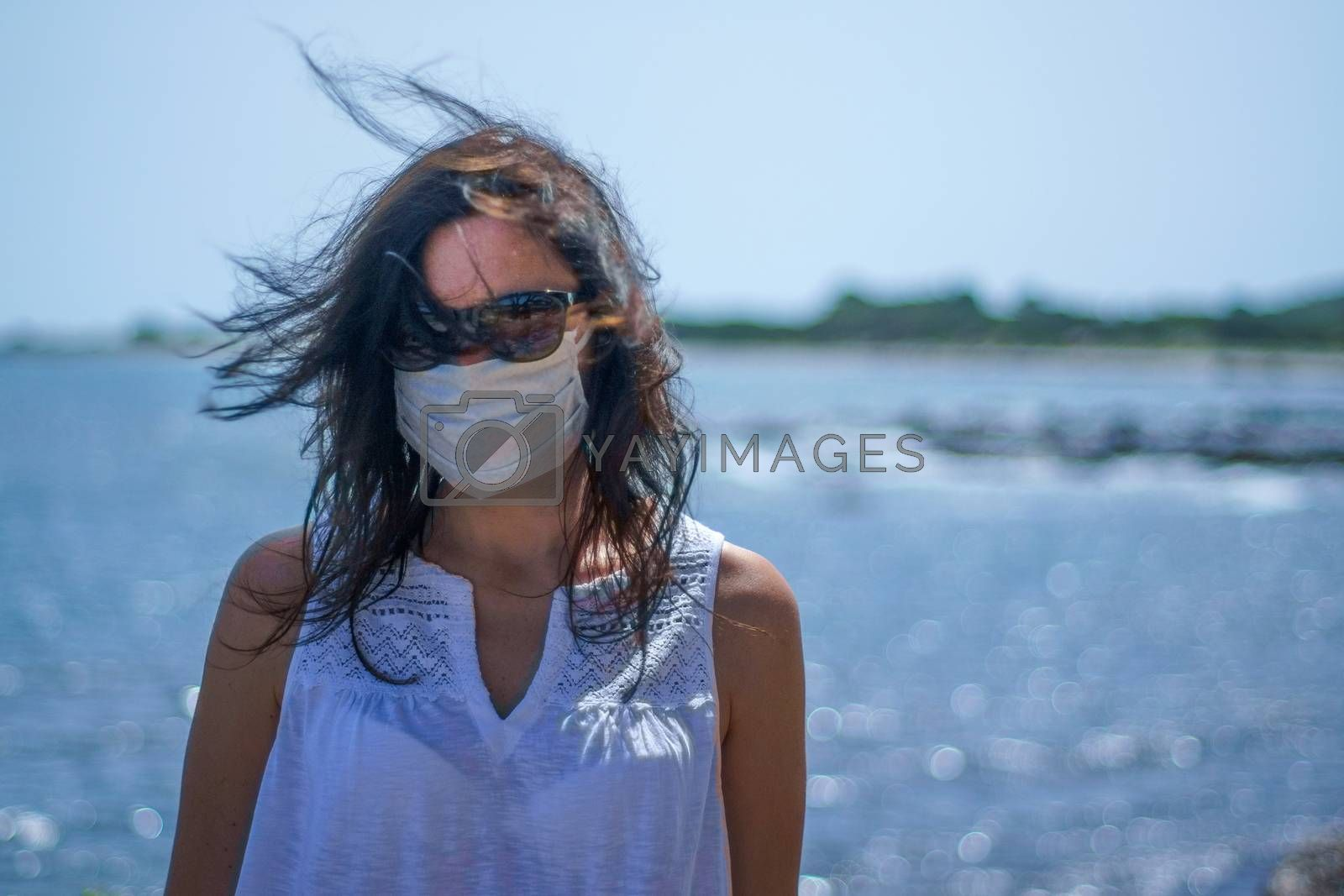 Coronavirus seaside holidays: half-length shot of a woman at the beach with the mask for Covid-19 pandemic with cloudy sky