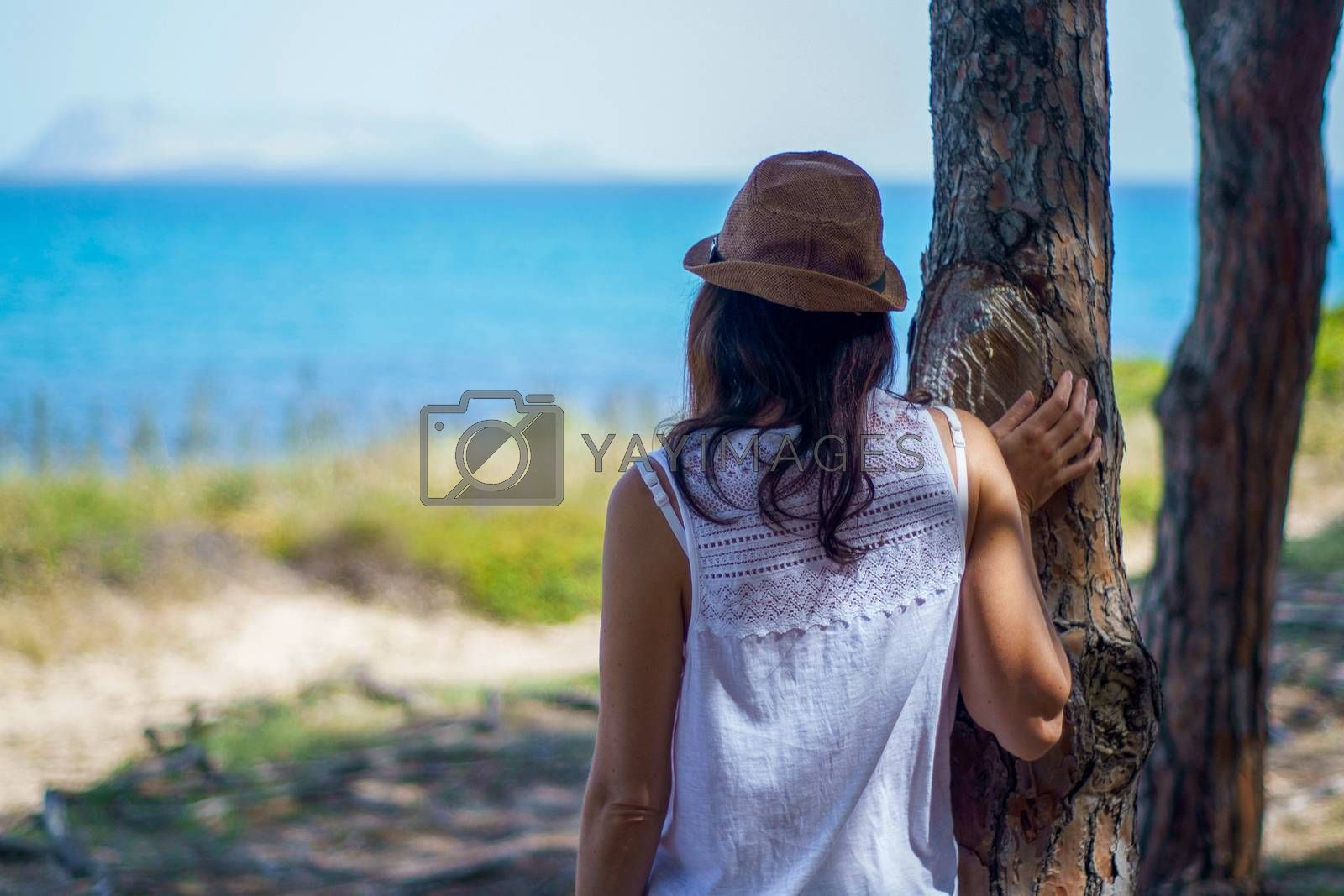 Pensive young woman with long hair and hat, seen from behind, looks at the sea leaning against a tree in a pine forest