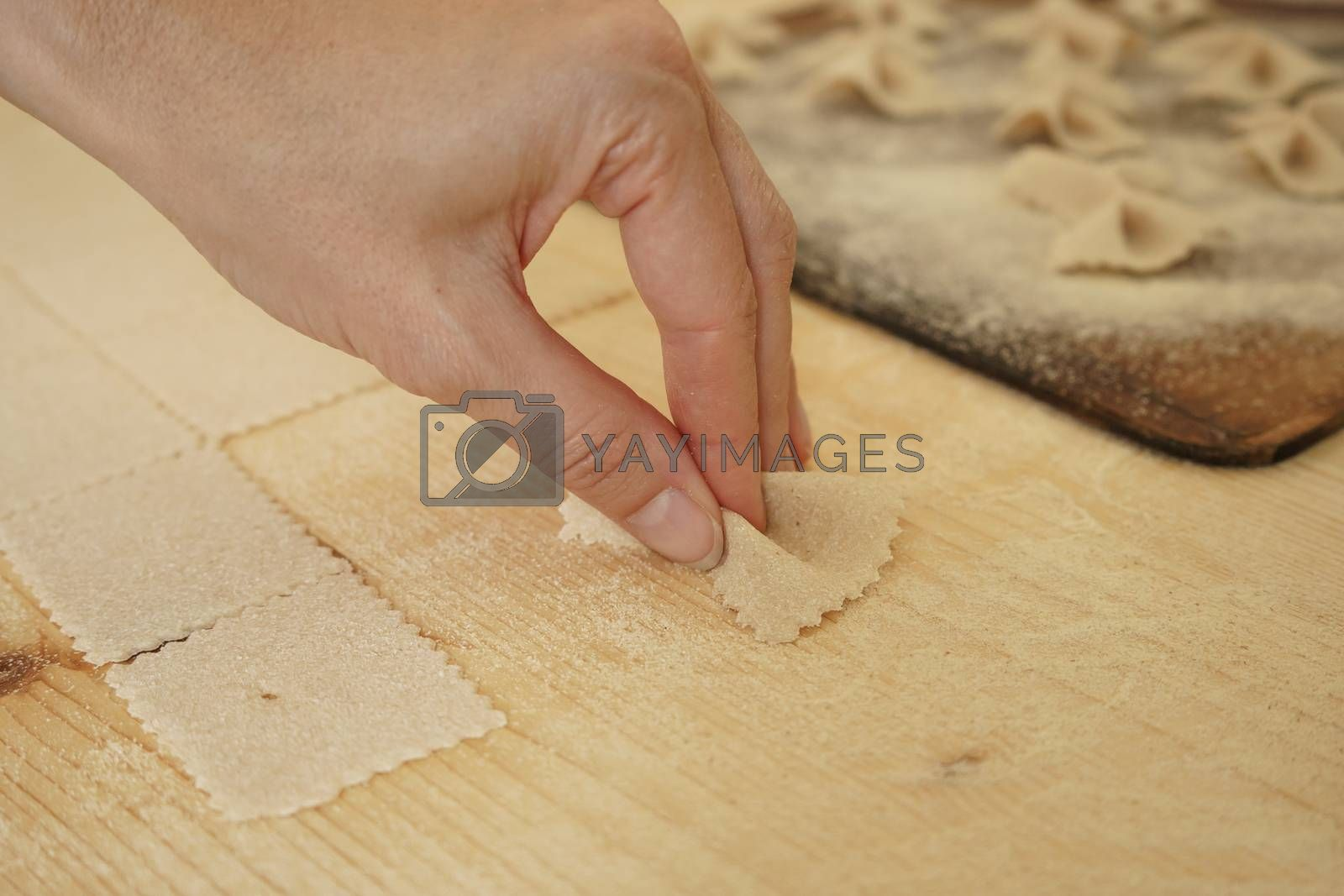 Close up macro detail of process of homemade vegan farfalle pasta with durum wheat flour. The cook kneads the dough on the wooden cutting board, traditional Italian pasta, the woman cooks the food