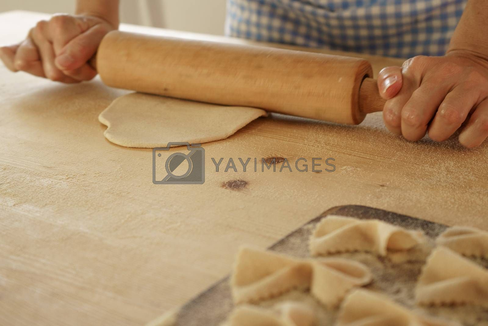 Close up process of homemade vegan farfalle pasta with durum wheat flour. The cook uses a rolling pin to stretch the dough, traditional Italian pasta, the woman cooks the food in the kitchen