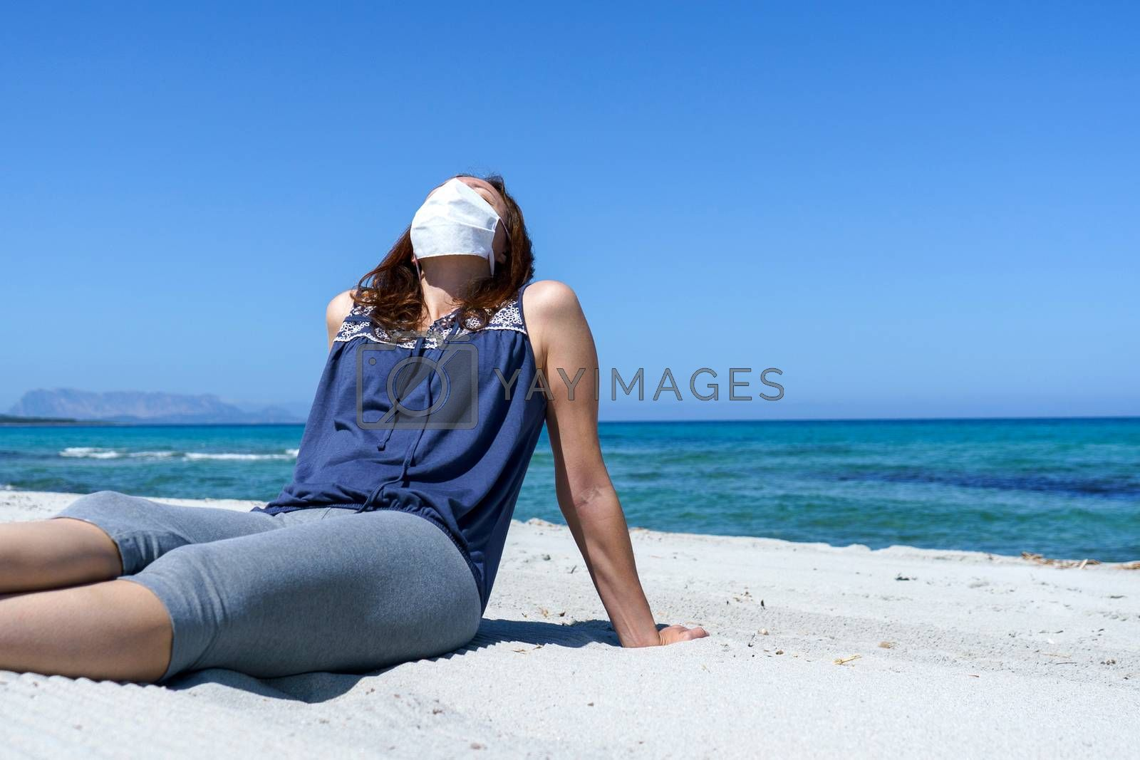 Coronavirus seaside holidays: a woman sitting on the sand at the beach look at the sun with the mask for Covid-19 pandemic