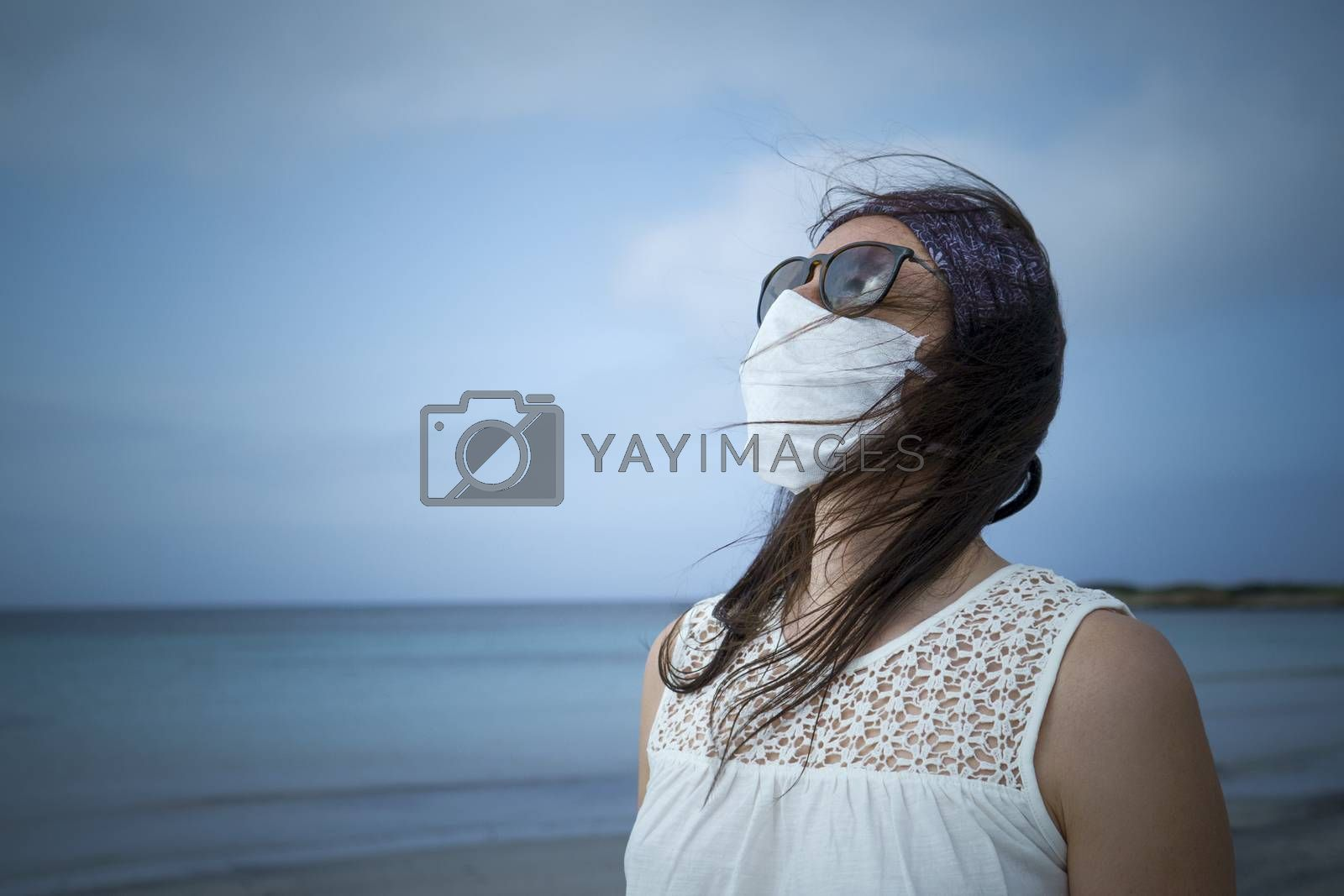 Coronavirus seaside holidays: half-length shot of a woman at the beach looking at the sun with the mask for Covid-19 pandemic