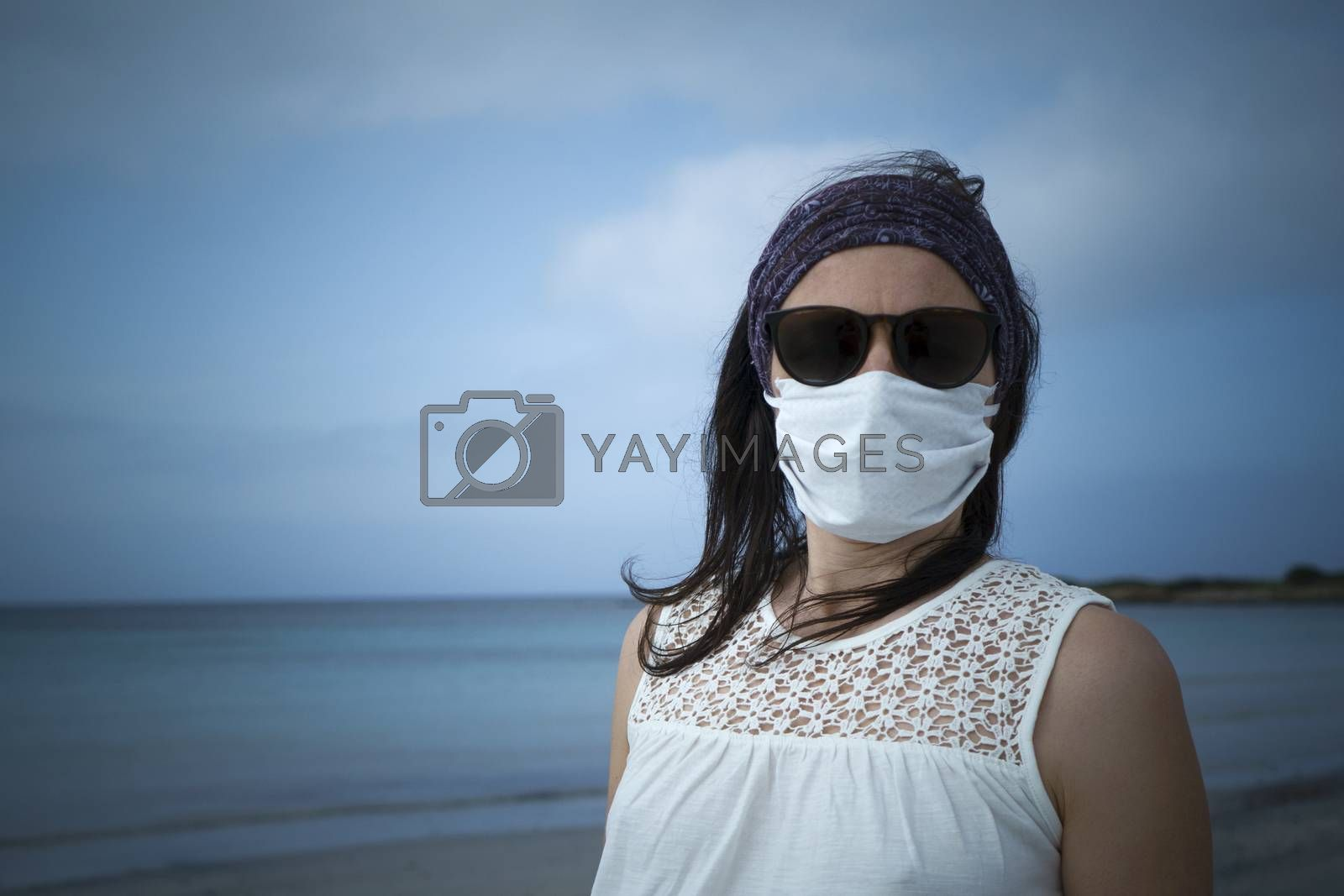 Coronavirus seaside holidays: half-length shot of a woman at the beach look at the camera with the mask for Covid-19 pandemic with cloudy sky