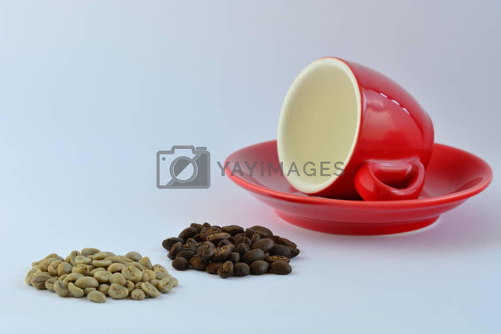 A close-up photo of a bright red espresso coffee cup, some green coffee beans and some roasted coffee beans on white background.