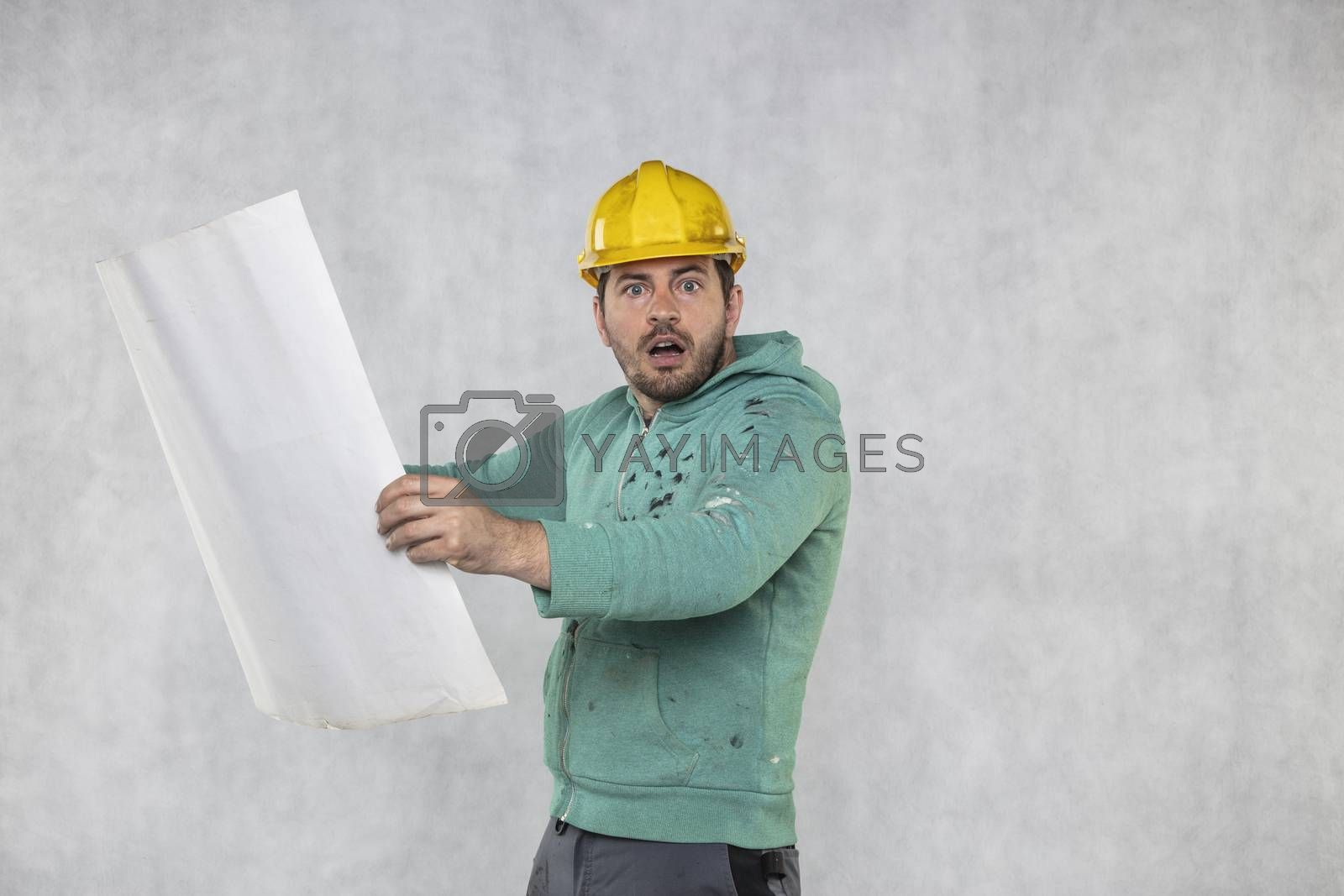 Surprised construction worker is reviewing construction plans