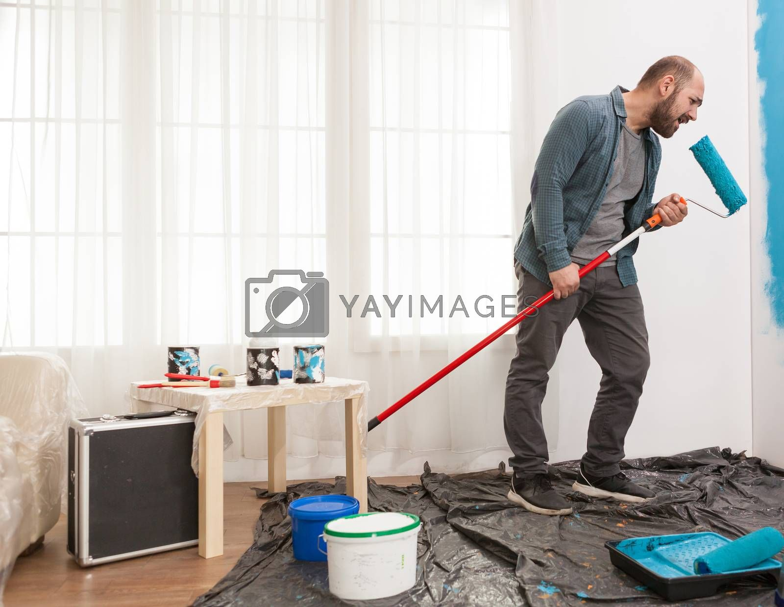 Happy husband singing at a roller brush while painting a blue wall. House decoration, brush, teamwork. Home decoration and renovation in cozy apartment flat, repair and makeover