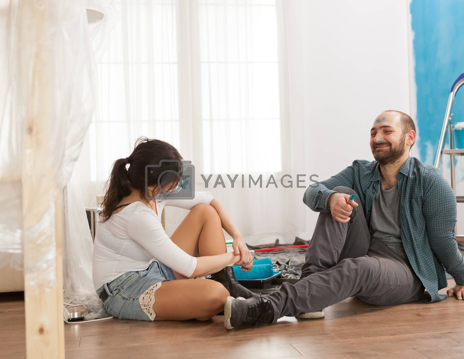 Tired and happy couple, painted on the face, sitting on the floor after renovation. Apartment redecoration and home construction while renovating and improving. Repair and decorating.
