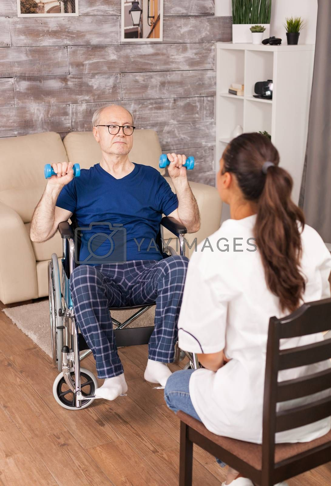 Medical worker explaining the exercises to old person in wheelchair. Disabled handicapped old person with social worker in recovery support therapy physiotherapy healthcare system nursing retirement home