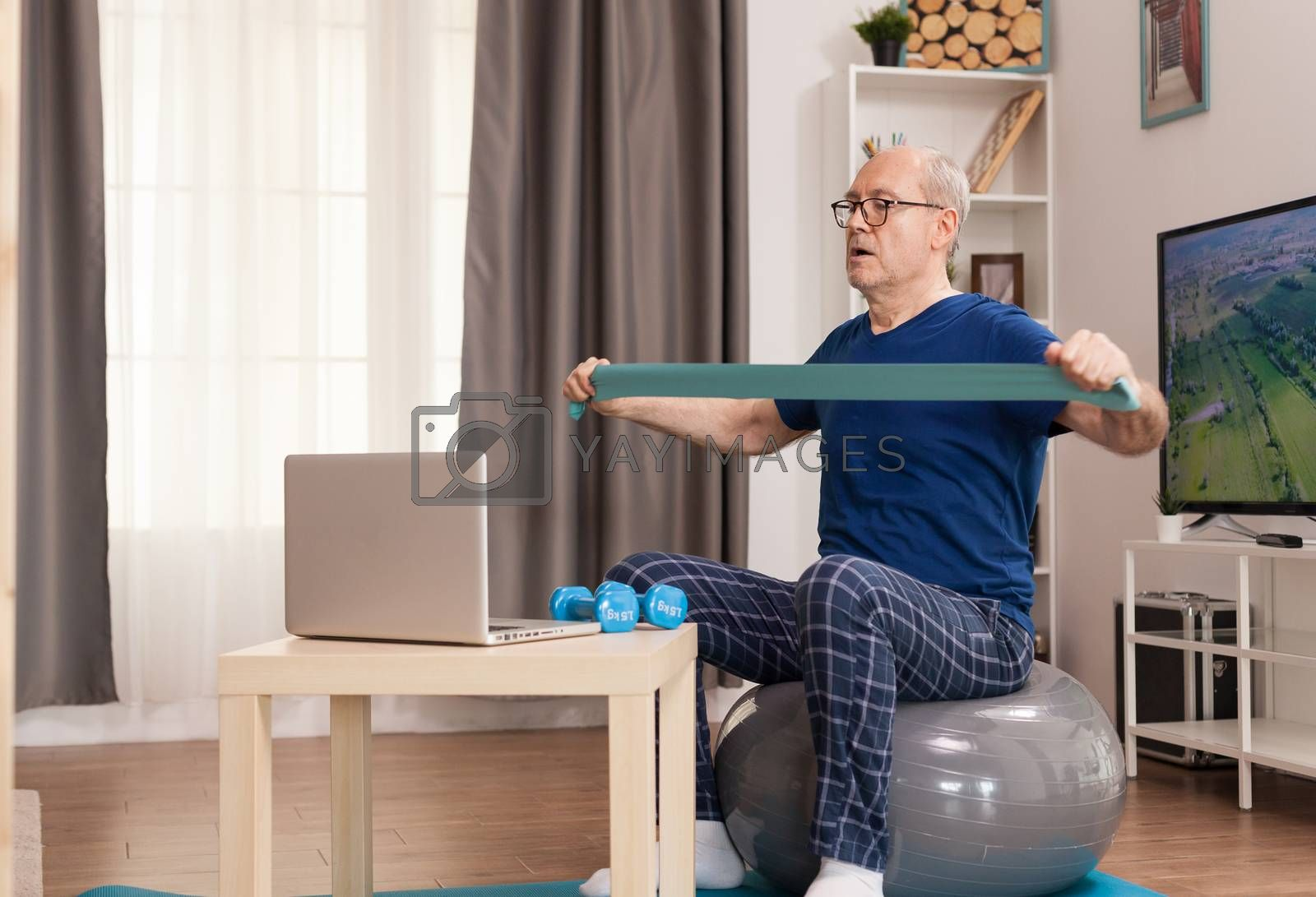 Strong old man training online with resistance band. Old person pensioner online internet exercise training at home sport activity with dumbbell, resistance band, swiss ball at elderly retirement age.