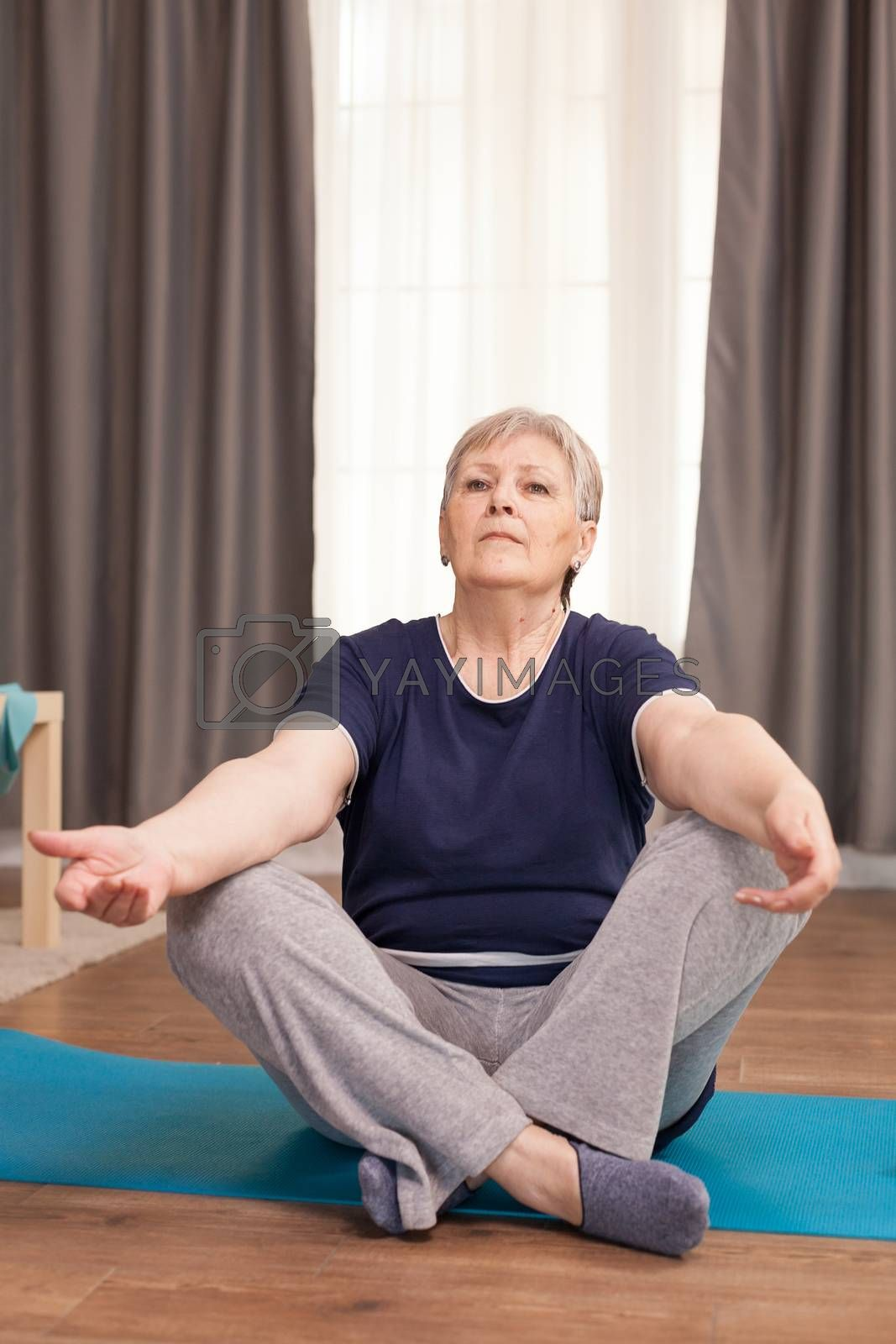 Portrait of old woman practicing yoga for a healthy body. Old person pensioner online internet exercise training at home sport activity with dumbbell, resistance band, swiss ball at elderly retirement age
