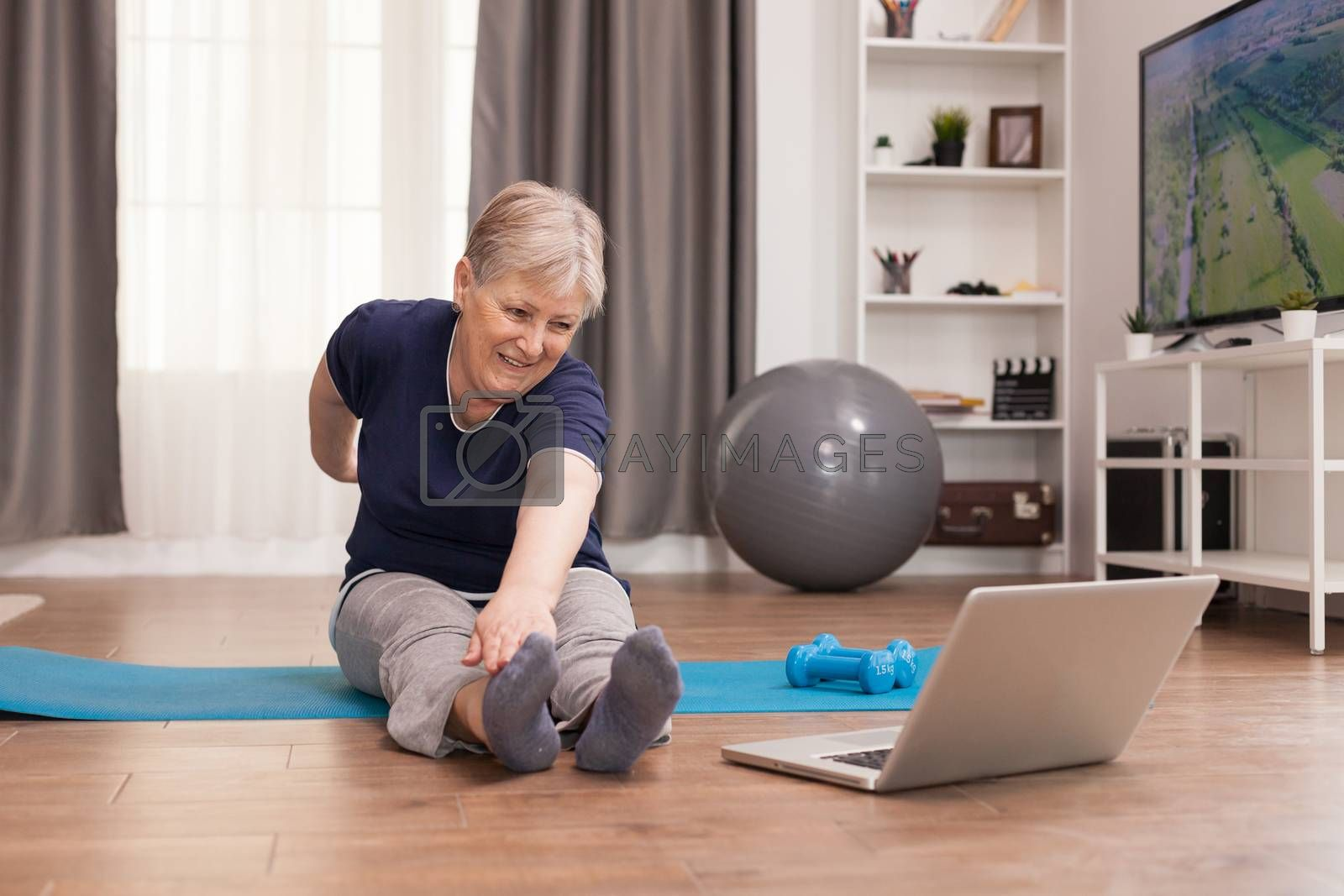 Cheerful old woman doing sports watching online lessons. Old person pensioner online internet exercise training at home sport activity with dumbbell, resistance band, swiss ball at elderly retirement age