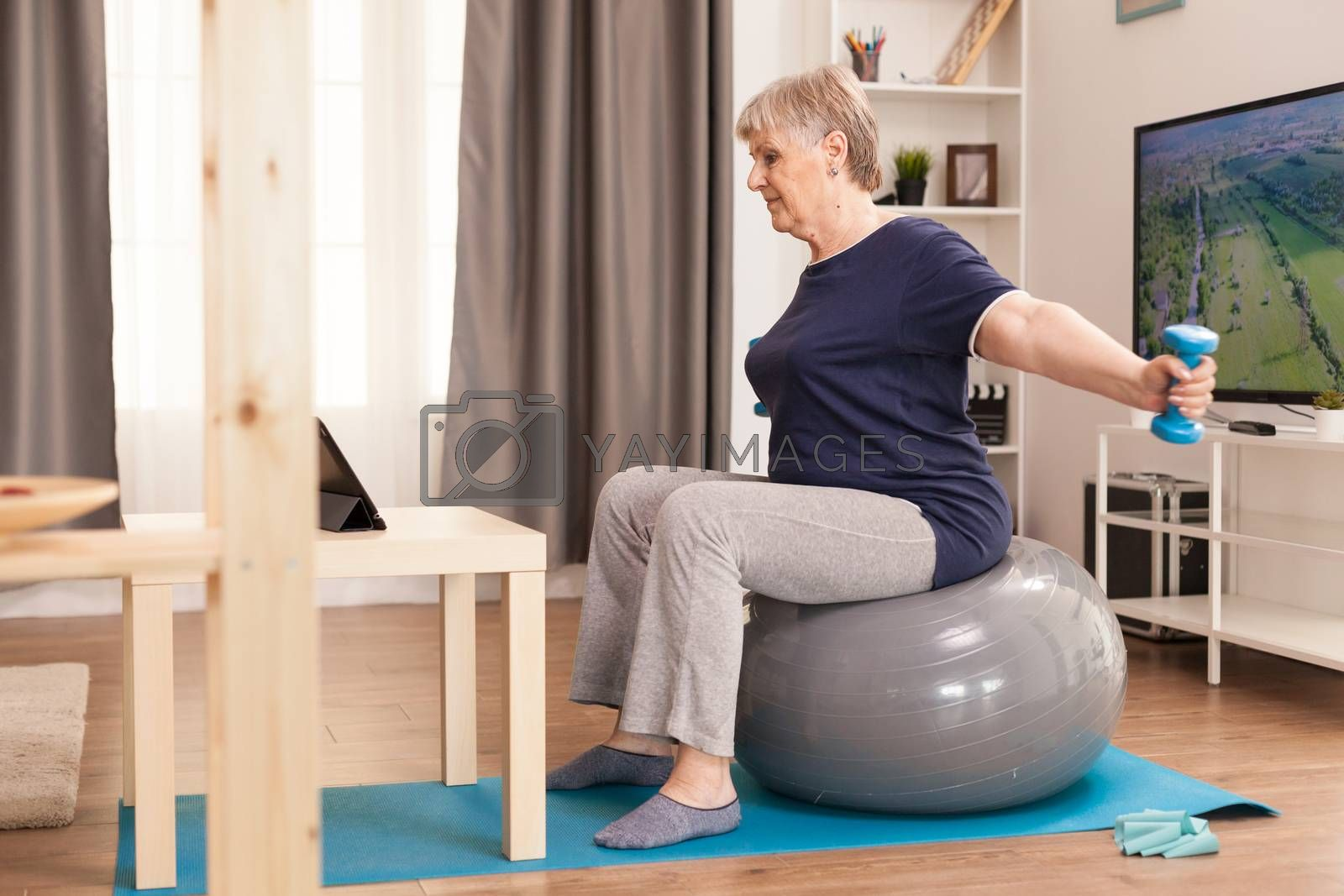 Grandma doing sports in pajamas with personal trainer online. Old person pensioner online internet exercise training at home sport activity with dumbbell, resistance band, swiss ball at elderly retirement age