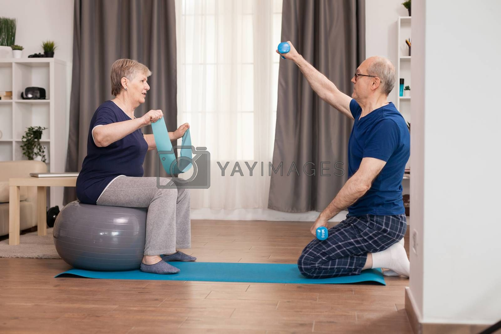 Active grandparents doing sports at home. Old person healthy lifestyle exercise at home, workout and training, sport activity at home on yoga mat.