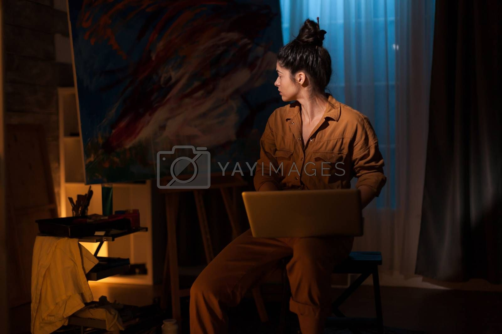 Young painter searching for inspiration on laptop in art studio. Modern artwork paint on canvas, creative, contemporary and successful fine art artist drawing masterpiece