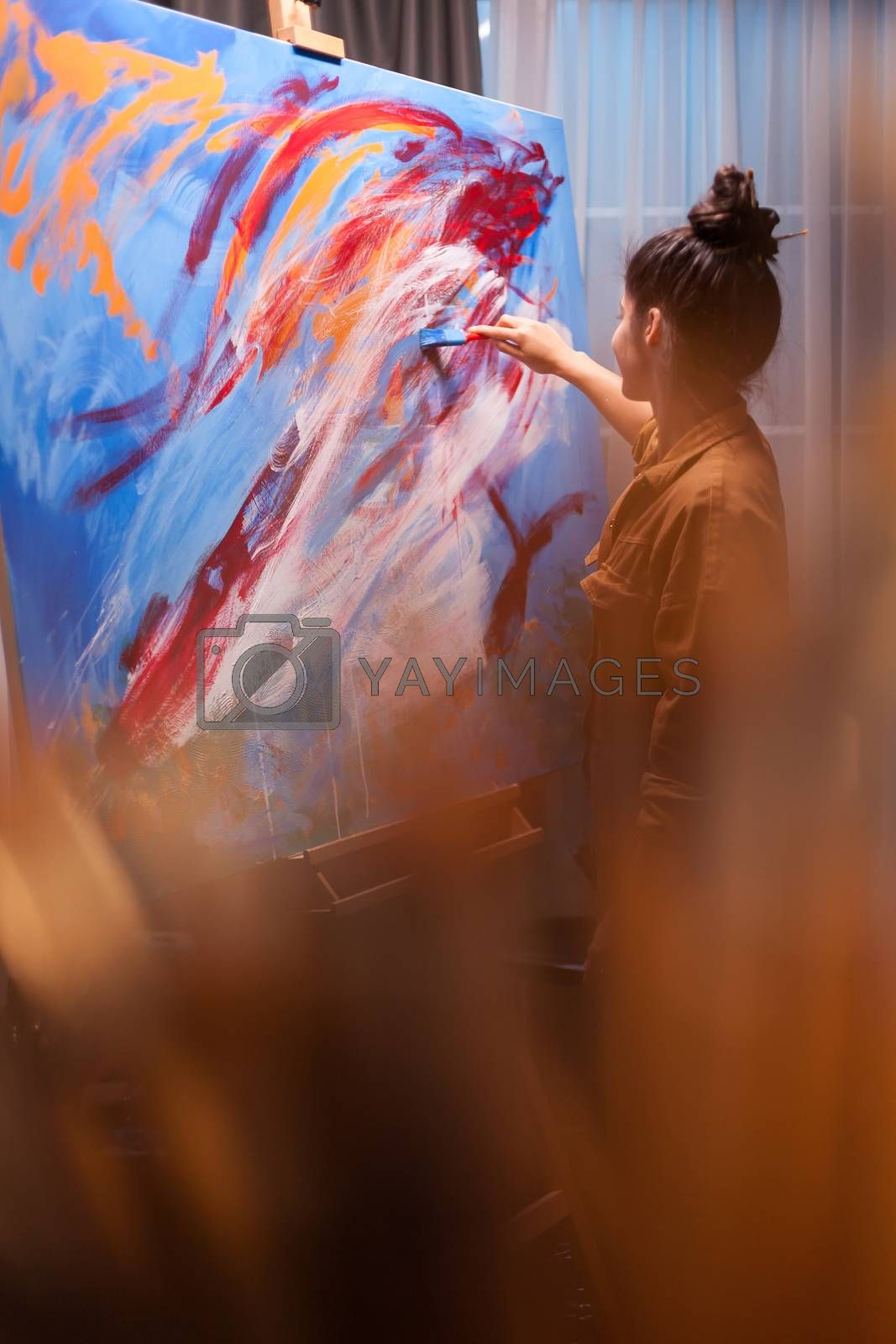 Woman in art studio painting on canvas. Colorful painting. Modern artwork paint on canvas, creative, contemporary and successful fine art artist drawing masterpiece