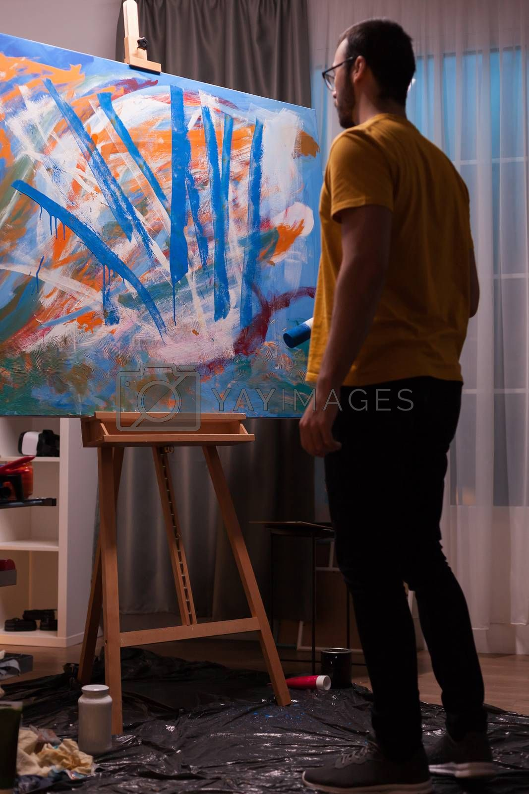 Abstract painter holding roller and looking at his masterpiece painting. Modern artwork paint on canvas, creative, contemporary and successful fine art artist drawing masterpiece