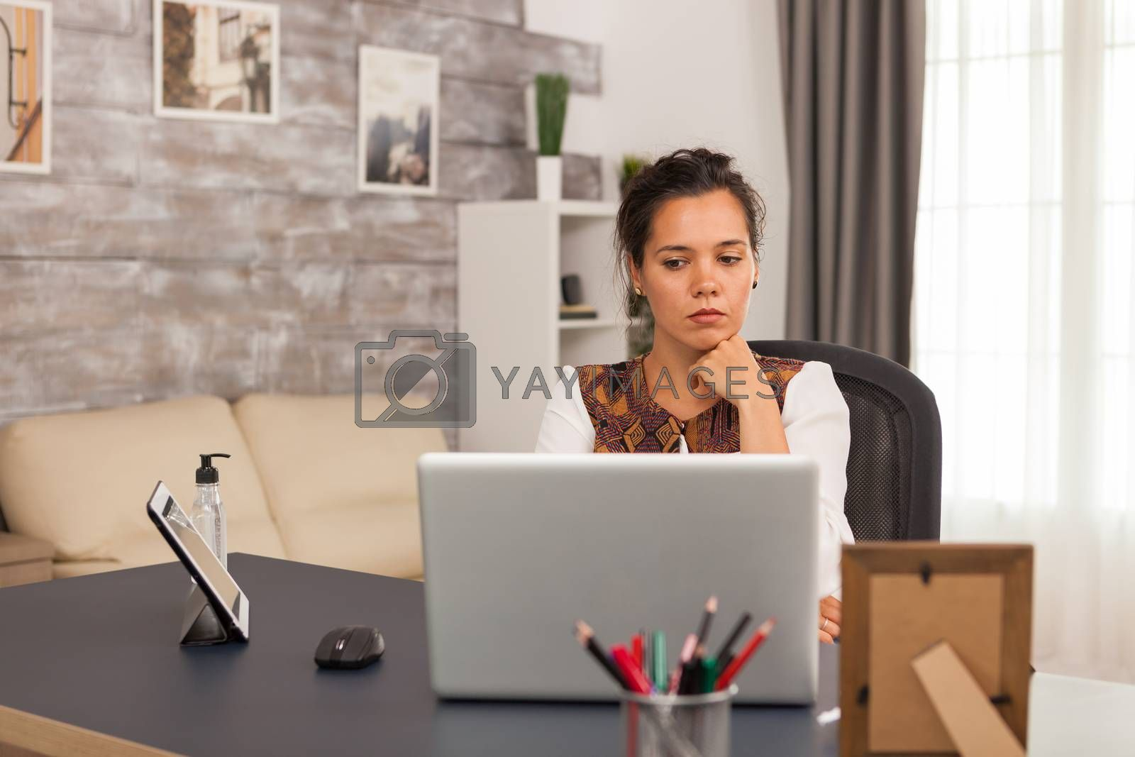 Focused female freelancer while working on laptop from home office.