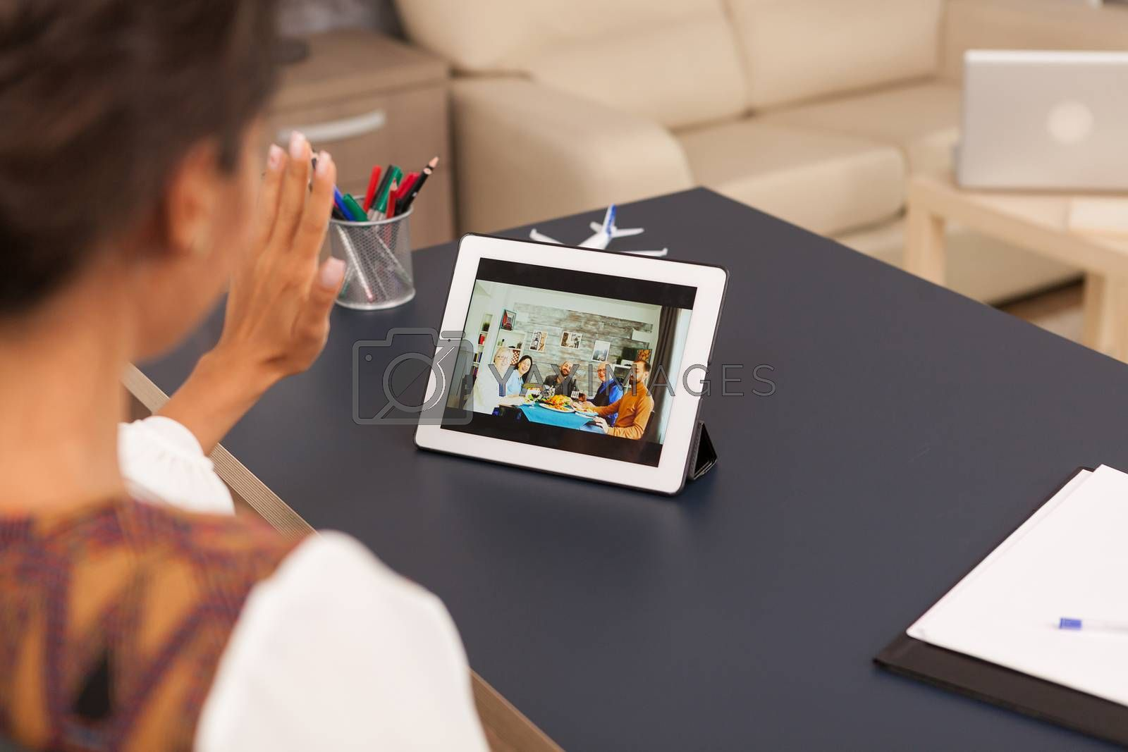 Waving at family during a video call on tablet computer.