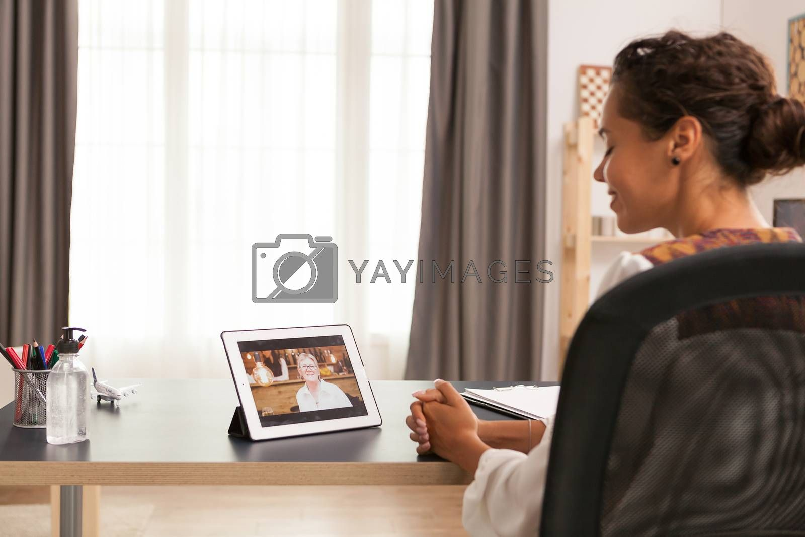 Woman talking with her mother during a video call on tablet computer.