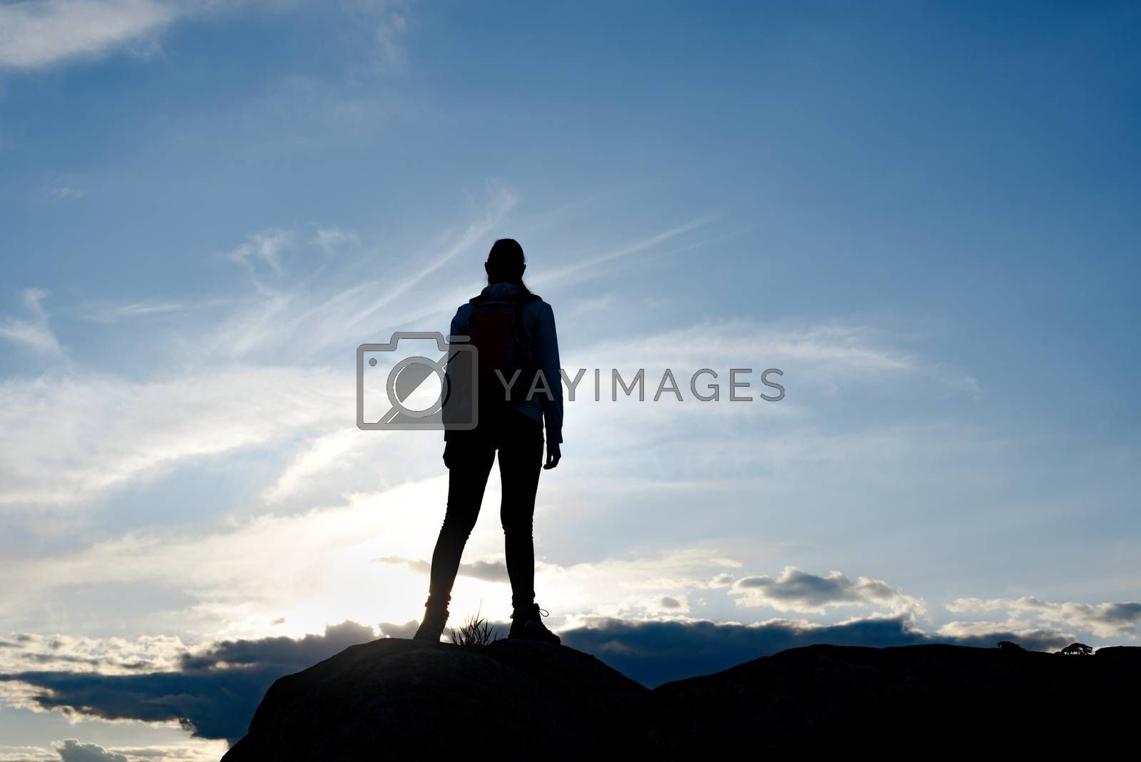 Young Woman Traveler with Backpack Standing on the Top of the Rock at Warm Summer Sunset. Travel and Adventure Concept.