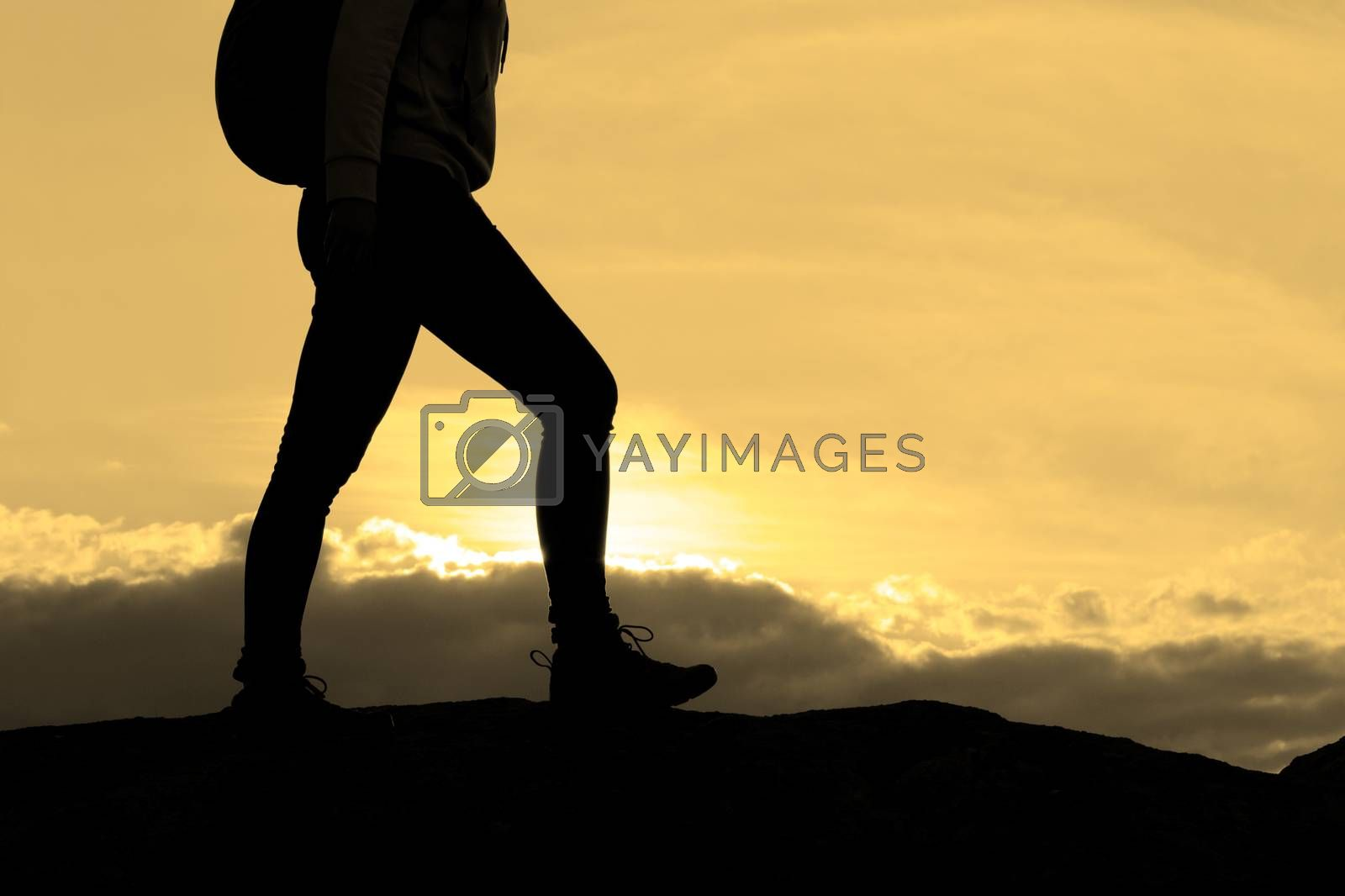 Hiker's Legs on the Rocky Trail at Warm Summer Sunset. Travel and Adventure Concept.