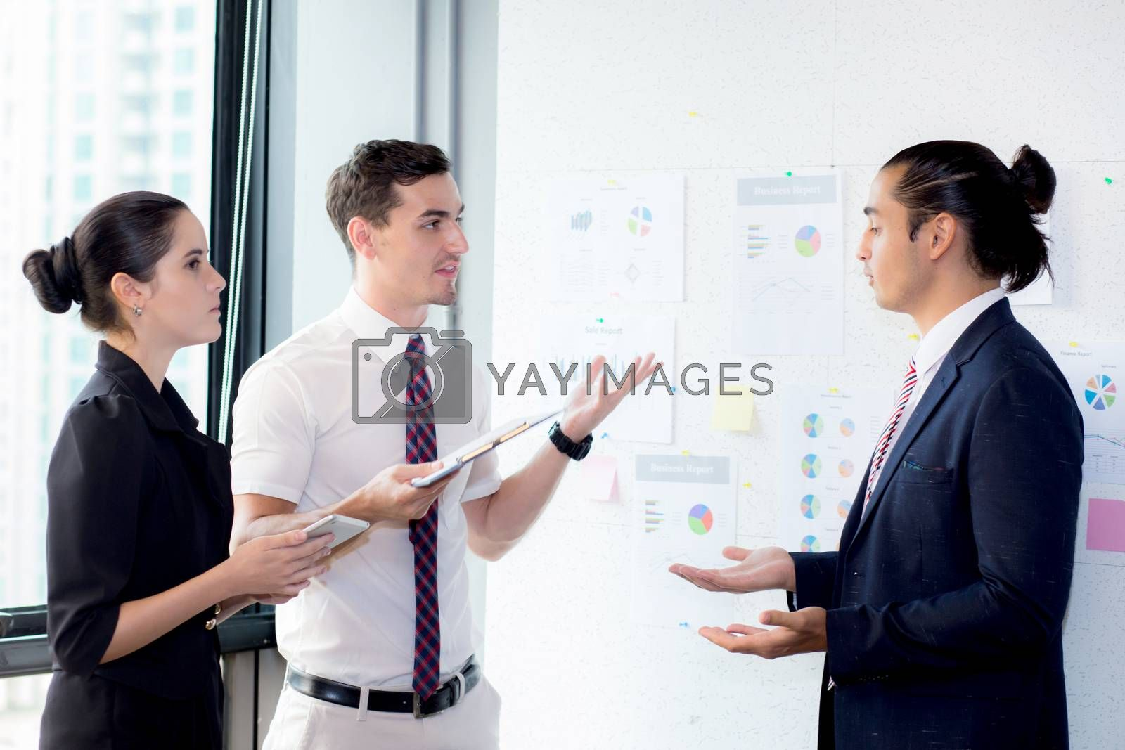Three businesspeople standing in modern office looking file docu by nnudoo