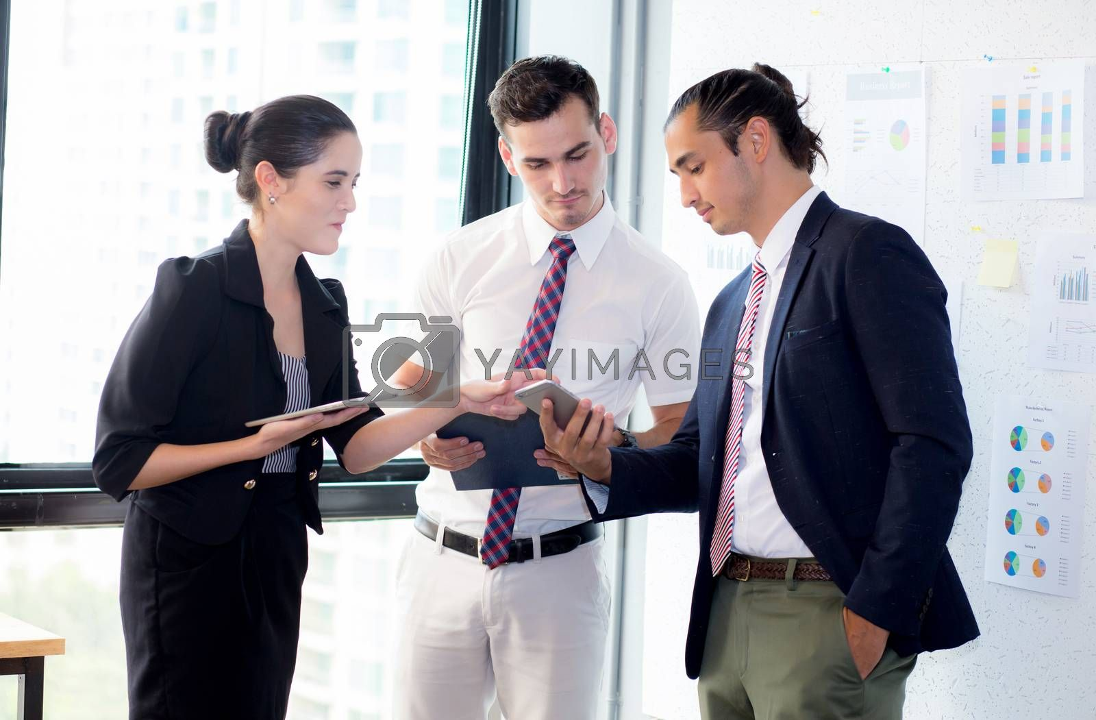 Three businesspeople standing in modern office looking at smart mobile phone and talking in meeting room.