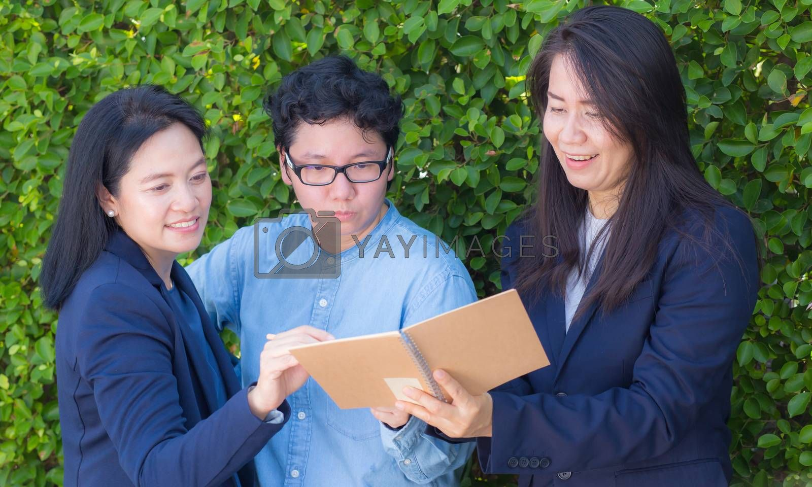 Businesswomen three people looking information on notebook or diary corporate on tree wall.