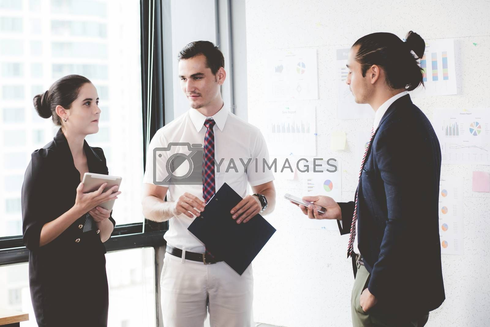 Three businesspeople standing in modern office looking file document and talking in meeting room.