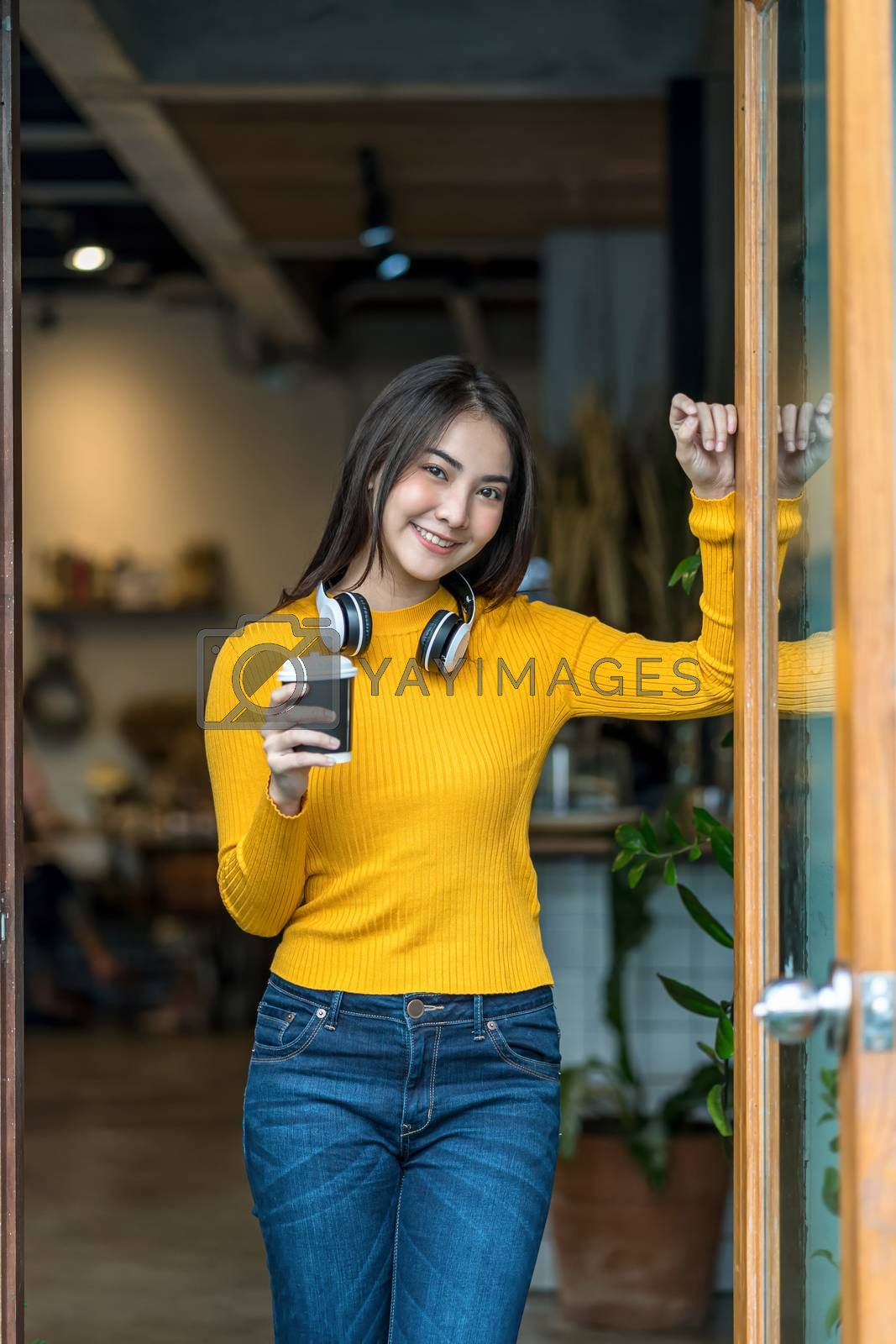 Asian young female holding a cup of coffee in modern coffee shop or coworking space beside coffee espresso machine, Lifestyle and leisure with hobby and entrepreneur concept