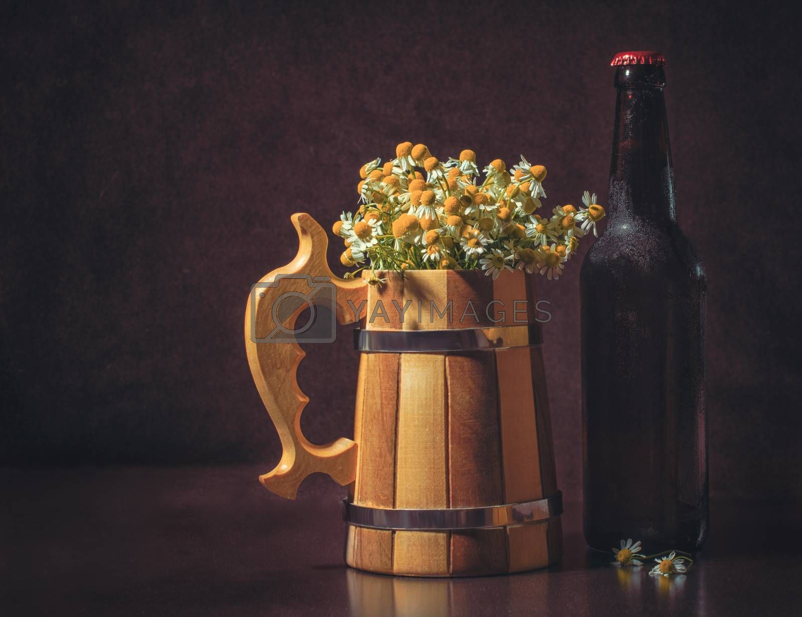 still life with a bottle of beer with a wooden mug and camomiles imitating foam on a dark brown background