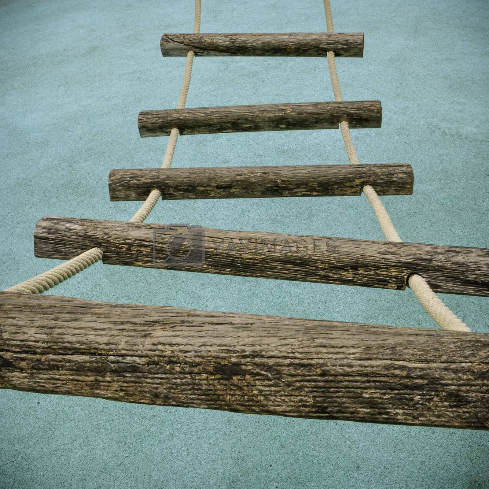 A perspective view of a rope ladder with wooden rungs on a children's climbing frame.