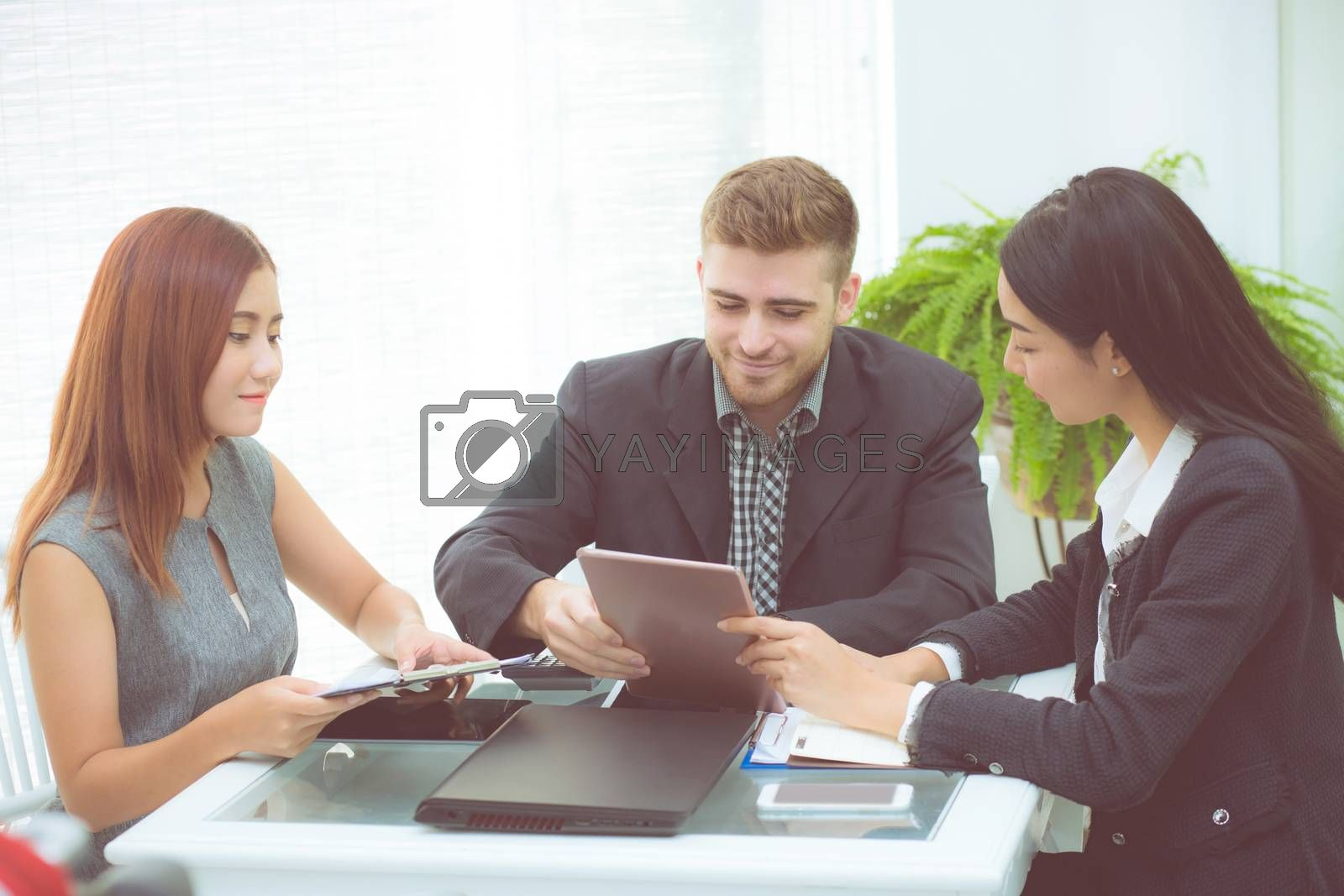 Asian young business people making meeting and looking at tablet for analyzing marketing working at office on desk.