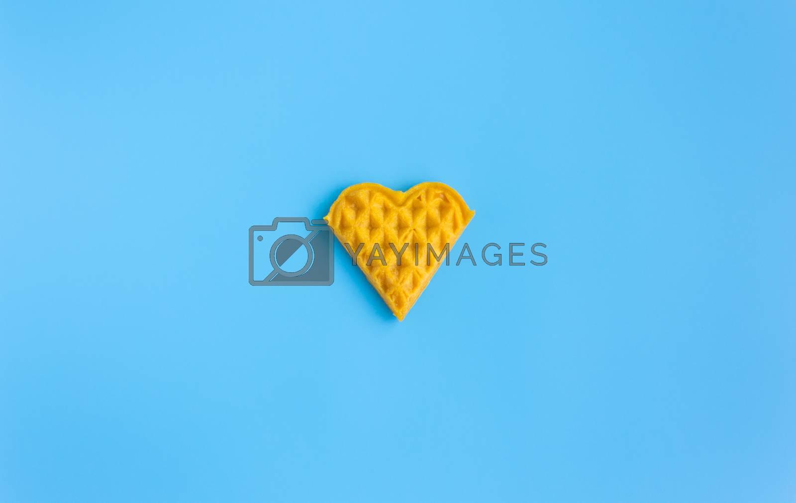 1 Piece Heart Shape Waffle on Blue Pastel Background Minimalist Style Wide Angle. Heart shape waffle dessert in minimalist style for food and dessert category
