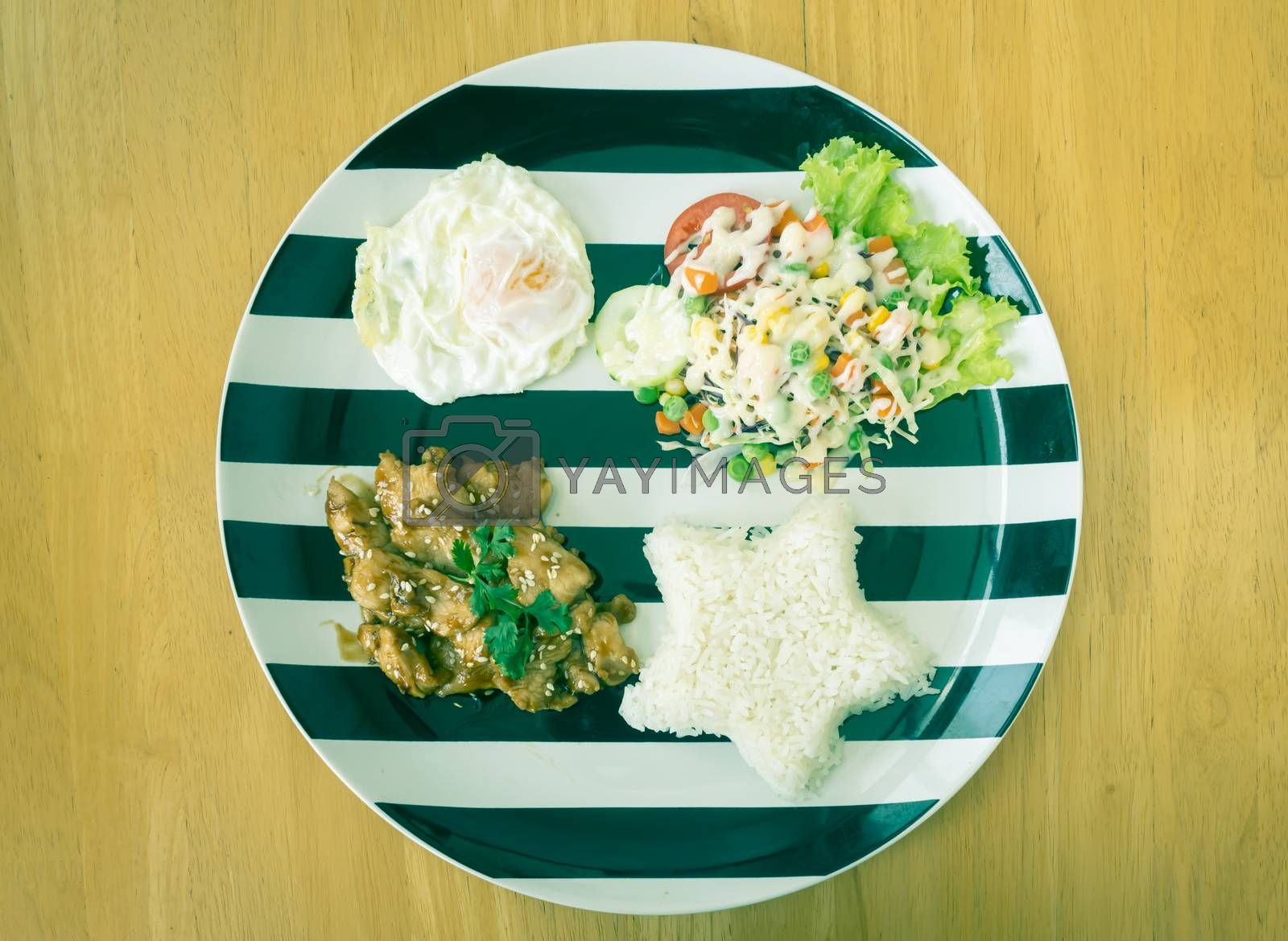 Fried Chicken with Garlic and Pepper and Fried Egg and Vegan Salad and Rice in Dish on Wood Table with Natural Light on Flatlay View in Vintage Tone